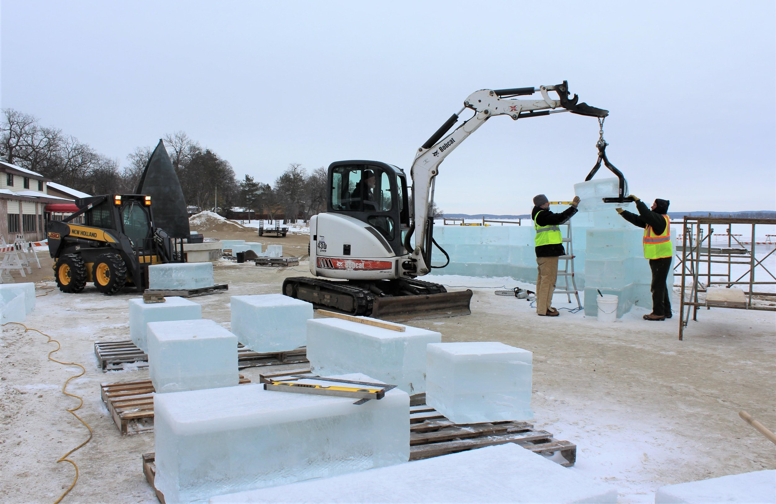 Volunteers on Wednesday stacked 600-pound blocks of ice on the City Beach near the Pavilion. Over the next three weeks, the blocks will be crafted into a decorative wall and throne structure as part of King Isbit's Royal Courtyard and Palatial Playground -- a highlight of this year's Polar Fest. (Marie Johnson / Tribune)