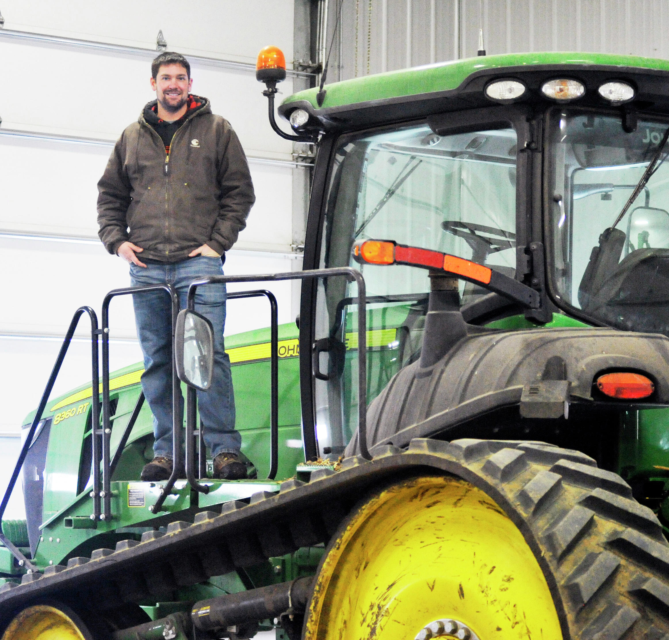 """Zach Johnson stands on the side of the tractor he used to film his viral """"Combine Karaoke"""" video. (Jared Rubado / Echo Press)"""