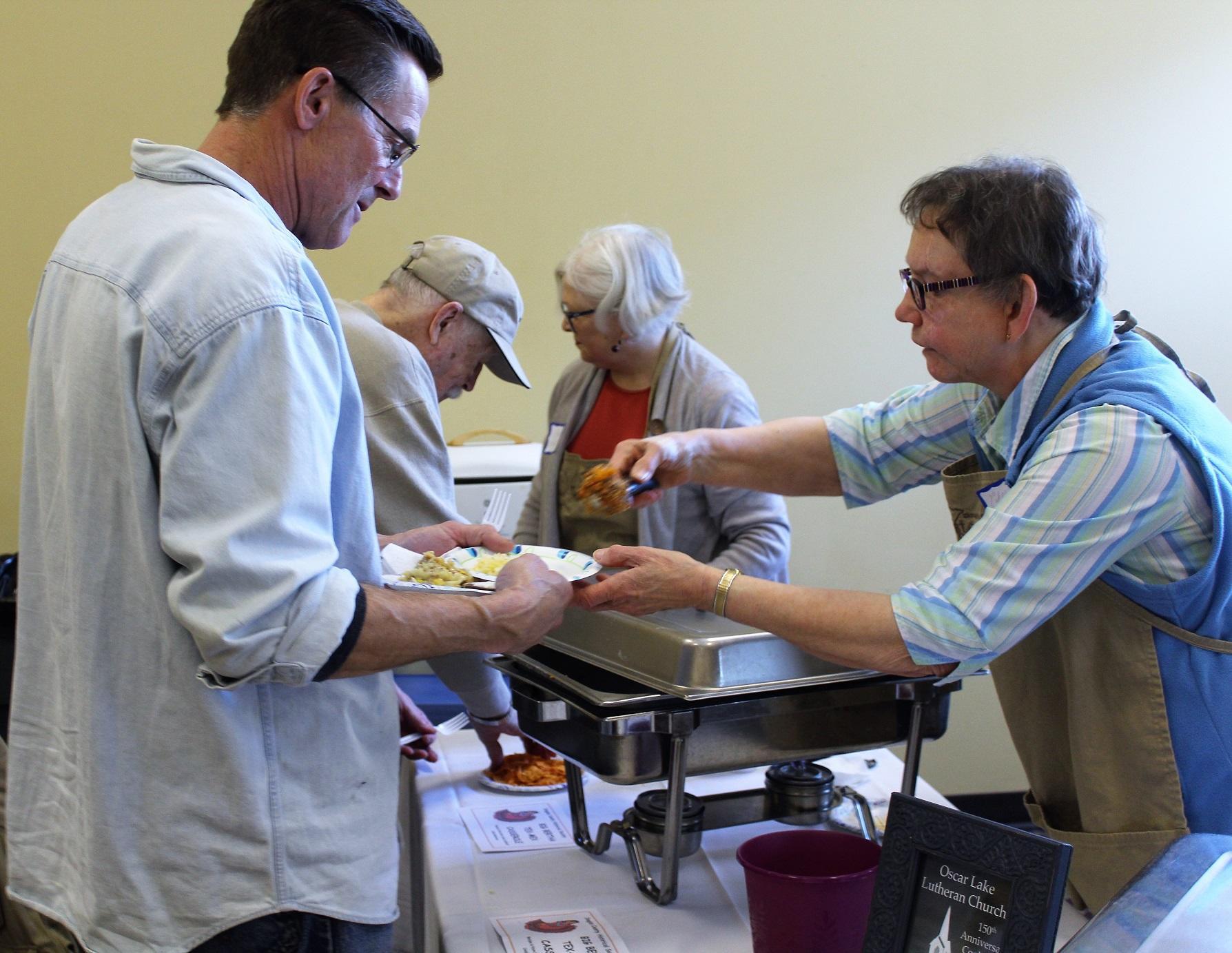 Char Hanson, a volunteer from the Douglas County Historical Society, serves hotdish to Wayne Freimuth of Miltona. The Big Bertha Tex-Mex Casserole, as it was labeled, came from the Oscar Lake Church cookbook. (Celeste Edenloff / Echo Press)