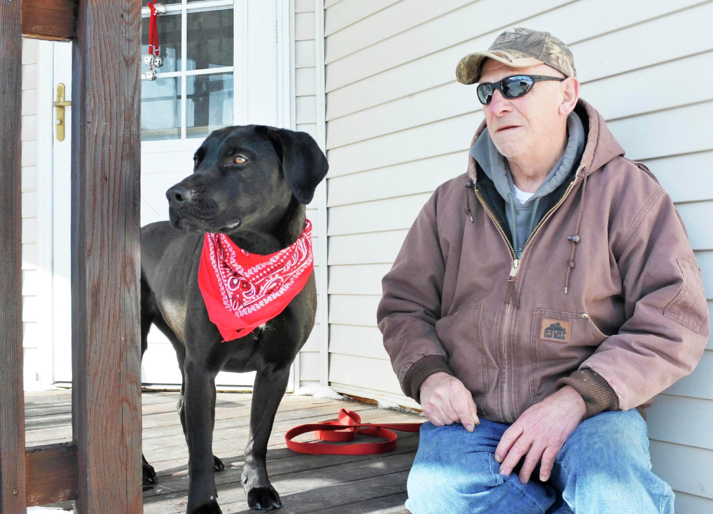 Tim Curfman, along with his black lab, Midnight, looks toward the house next door where they helped rescue their neighbor after she fell and couldn't get up on a cold day in early February. Midnight alerted Curfman that something was wrong. (Lowell Anderson / Echo Press)