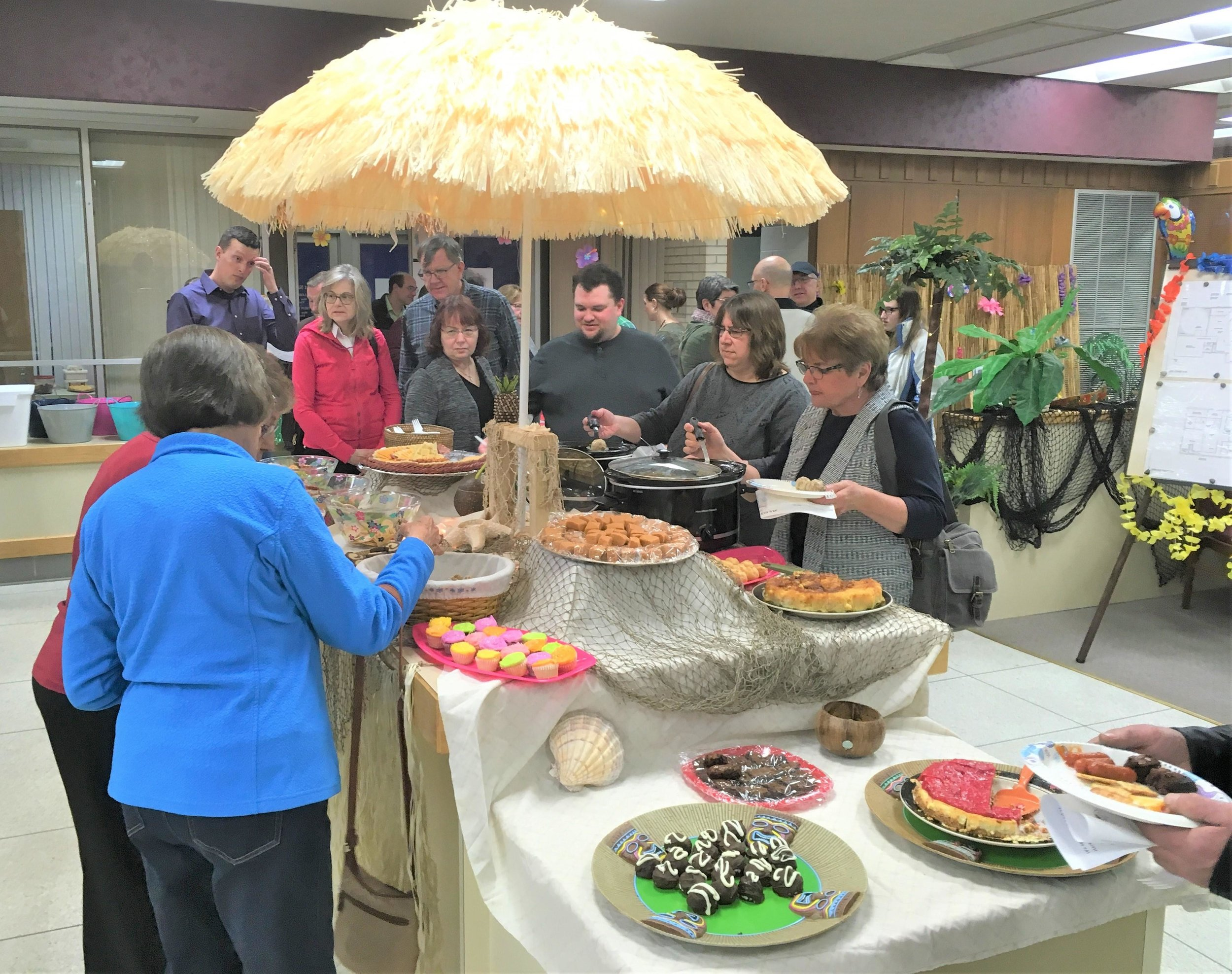 Under the shade of a grass umbrella, library fundraiser attendees indulged on meats, cheese, and confectionery delights Saturday at the former First National Bank building in Wadena. Michael Johnson/Pioneer Journal