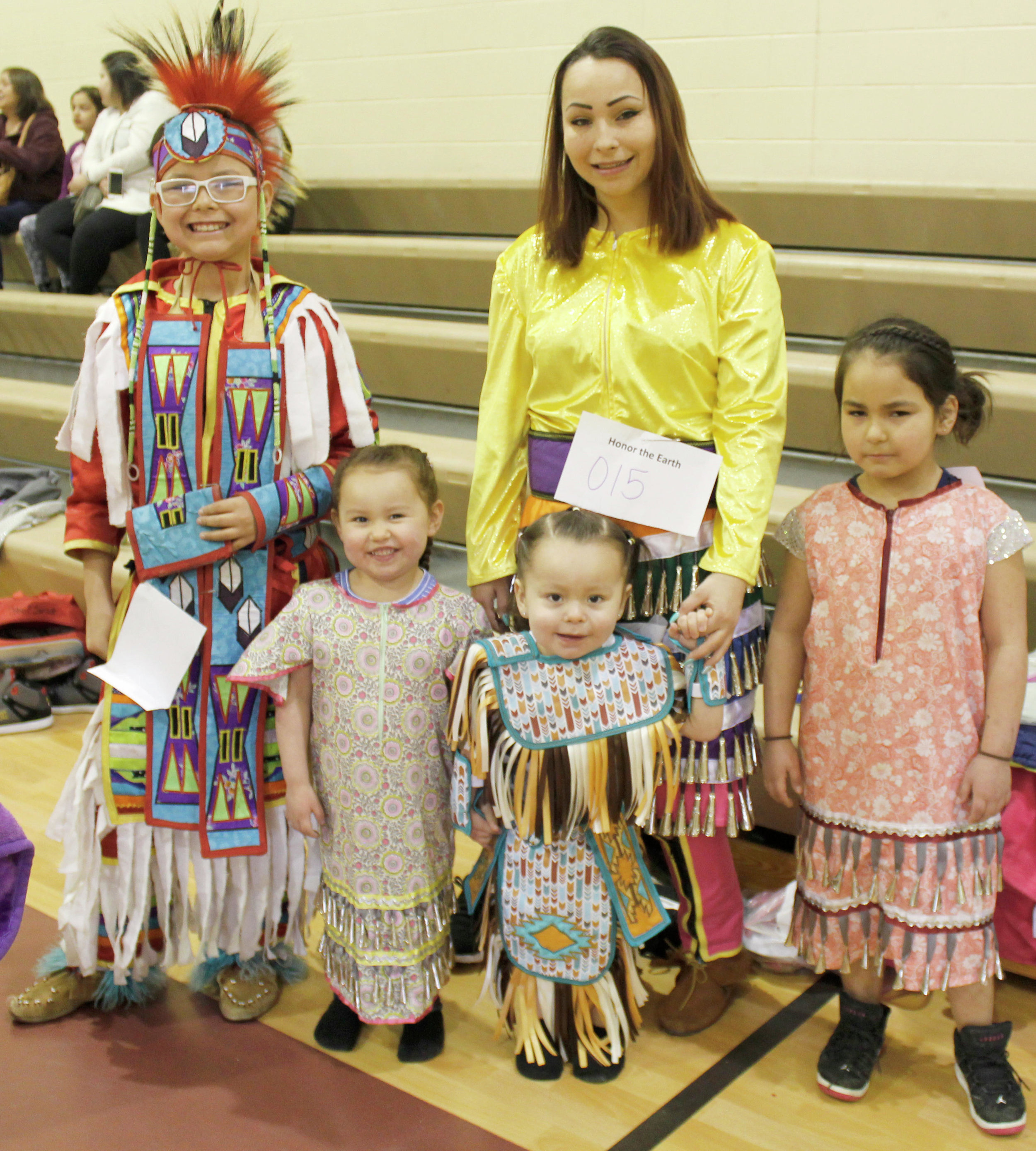 Kathi Larson and her children, Keagan Goodman, Tylie Smith, Tyler Smith and Tacia Beauchamp prepare to represent the White Earth Band of Ojibwe at the opening of Saturday's powwow.