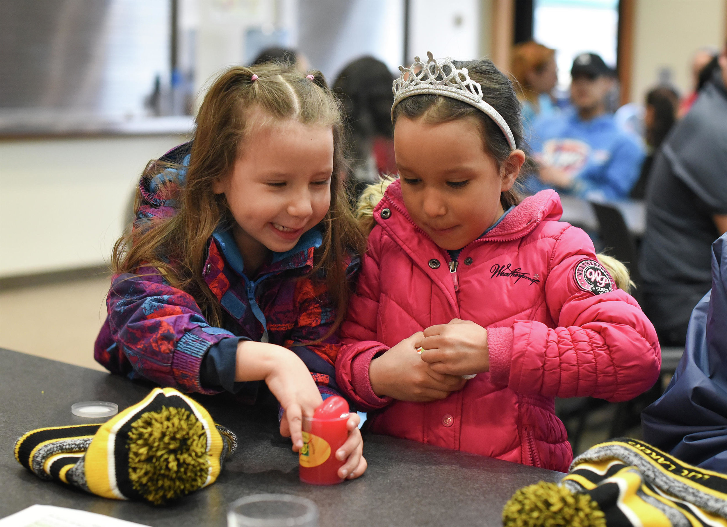 Lynnea White, 5, and Ziinaa White, 6, play with slime at Leech Lake Tribal College's fourth annual Across the Universe event. (Jillian Gandsey | Bemidji Pioneer)