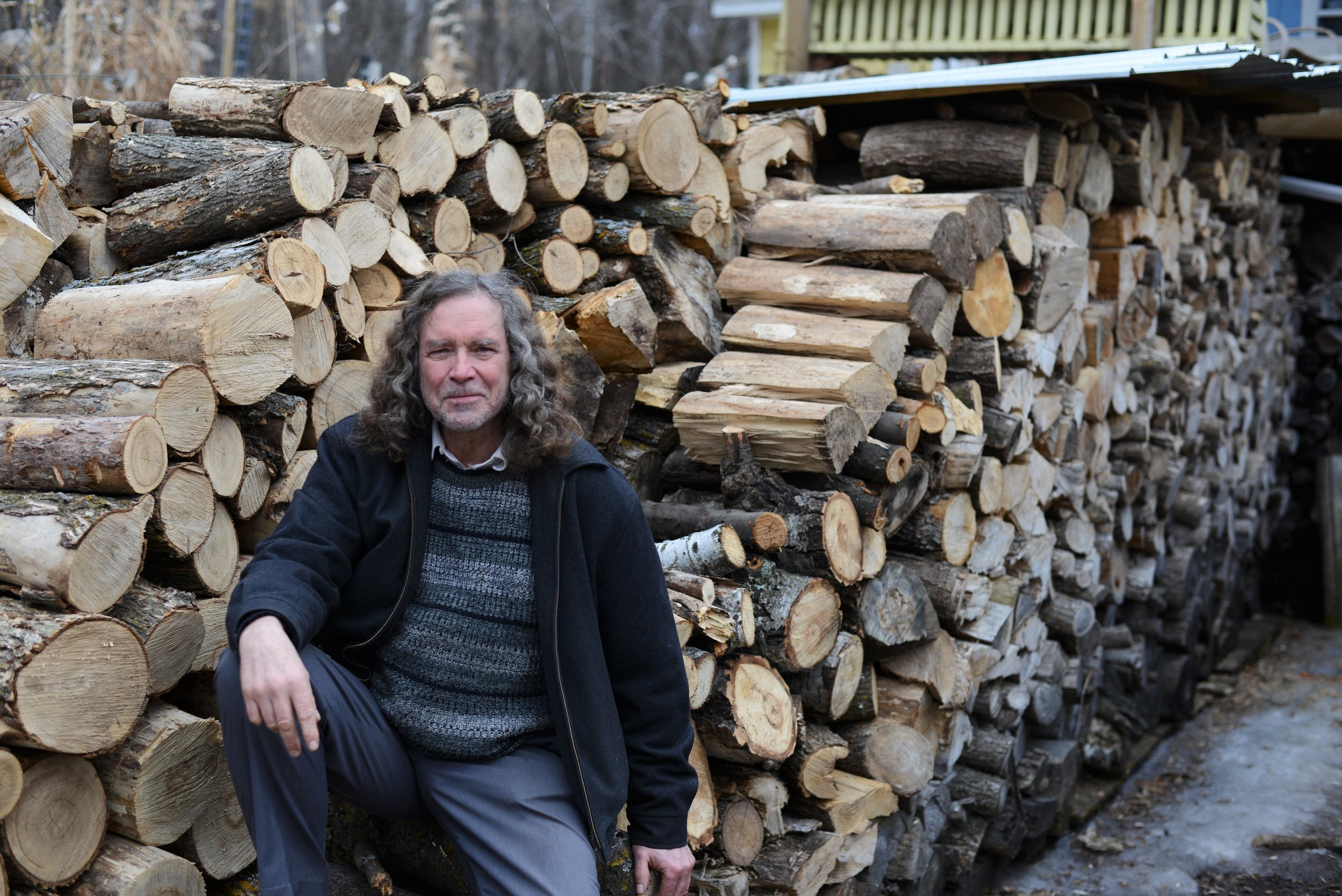 """Chuck Johnson poses for a portrait at his home north of Perham. """"I'm known for my woodpile,"""" Johnson said. (Carter Jones/ FOCUS)"""