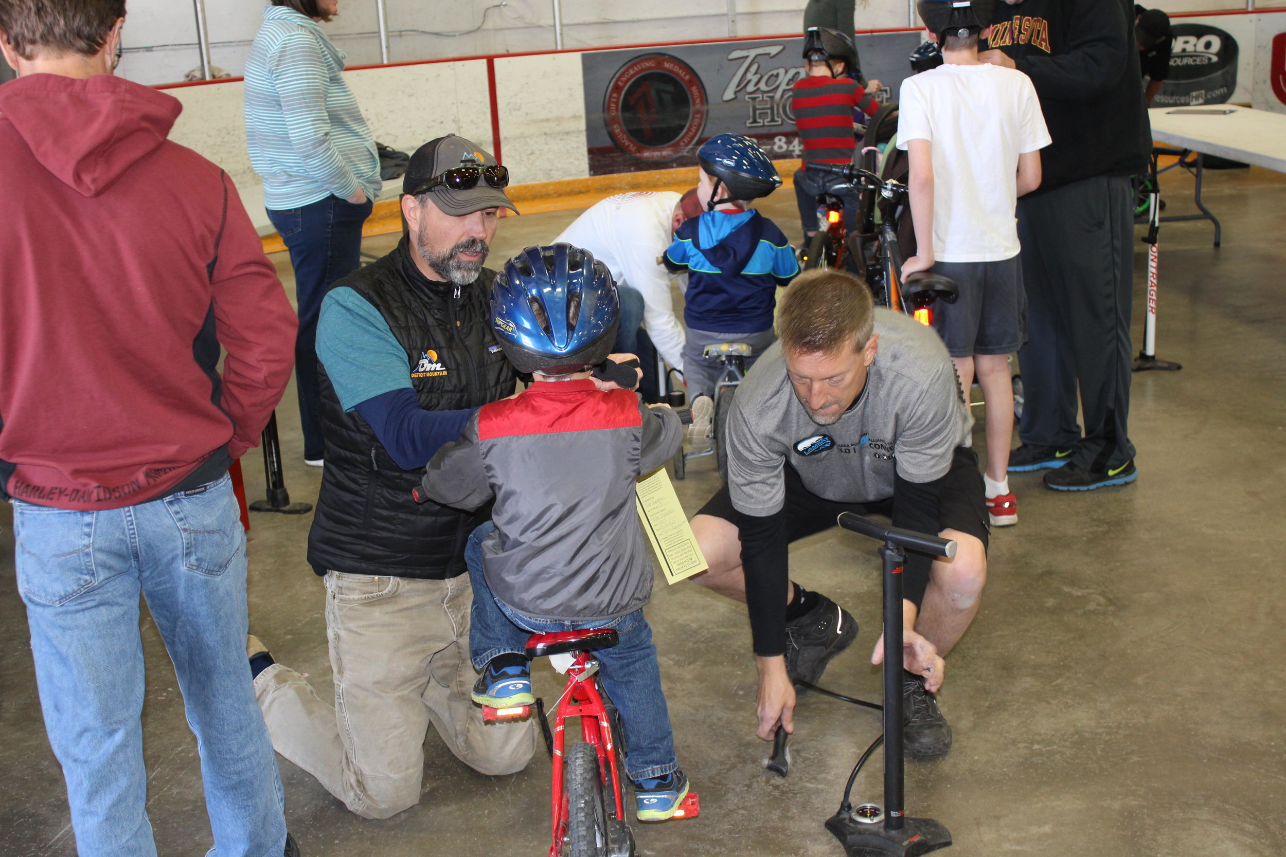 """Jeff Staley of Detroit Lakes (on knees) volunteered on the """"pit crew"""" making sure bikes were in good condition during the 2017 Bike Rodeo in Detroit Lakes. (Nathan Bowe / Tribune)"""