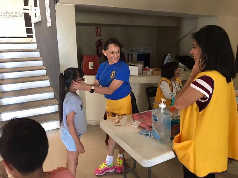 Mari Radke (center) shares a laugh with a Lions Club volunteer in Mazatlan as she fits a young girl with a pair of donated glasses during a recent eye care mission trip. (Submitted photo)