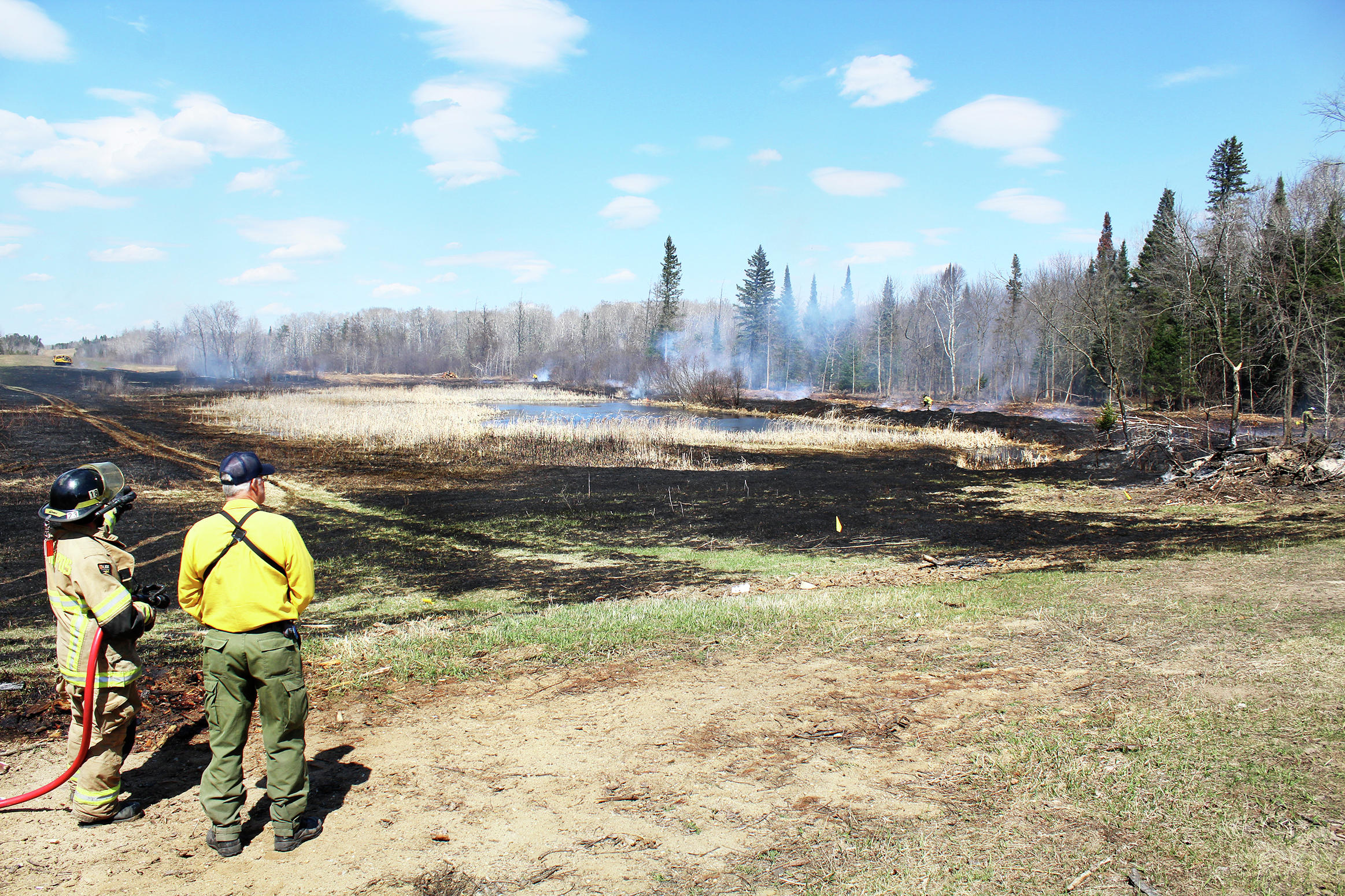 Approximately 12-14 Park Rapids firefighters and DNR foresters responded Thursday to a wildland fire on Impression Road. As containment efforts continued, Assistant Fire Chief Ben Cumber said the cause of the fire had not been determined, but it looked like an unattended brush fire. (Robin Fish/Enterprise)