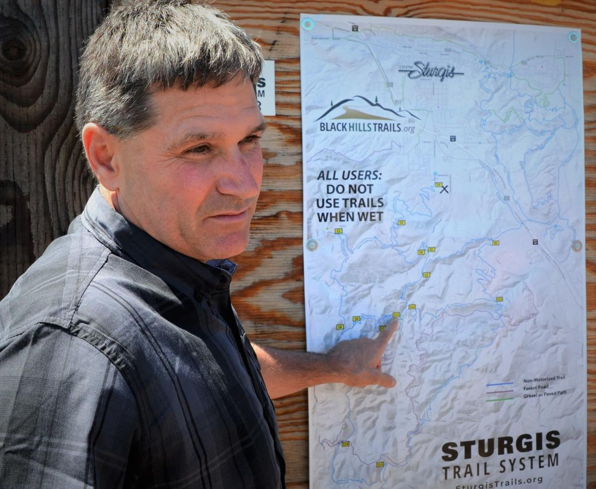 Kevin Forrester, of Black Hills Trails, shows a map of the recreational trail system posted at a trailhead in south Sturgis. Jim Holland / Rapid City Journal