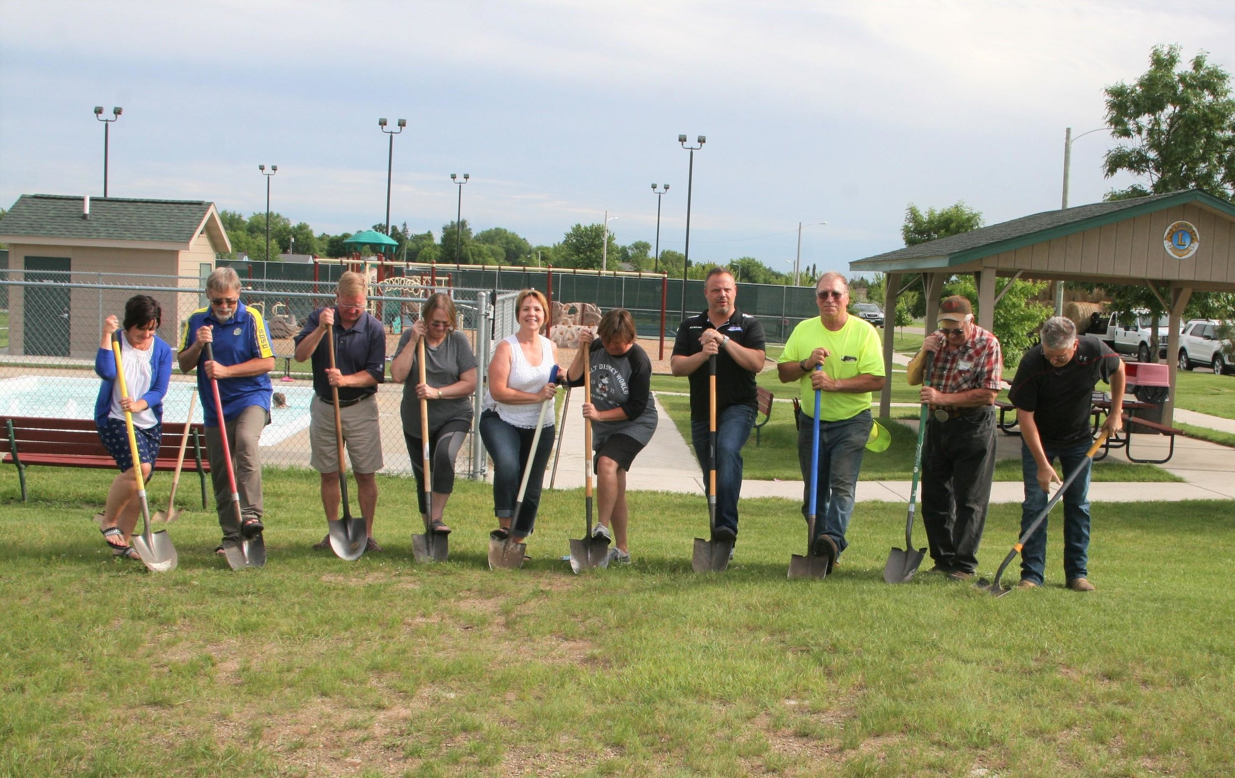 A group gathered to scratch the surface of the future splash pad in the southwest park next to the wading pool. They included Janette Bower, George Deiss, Dean Krogstad, Sandy Black, Deb Wiese, Sara Ross, Mark Lunde, Mike Pete, Larry DeWald and Dan Kovar. With the work to begin soon, completion could be done in August. Michael Johnson/Pioneer Journal