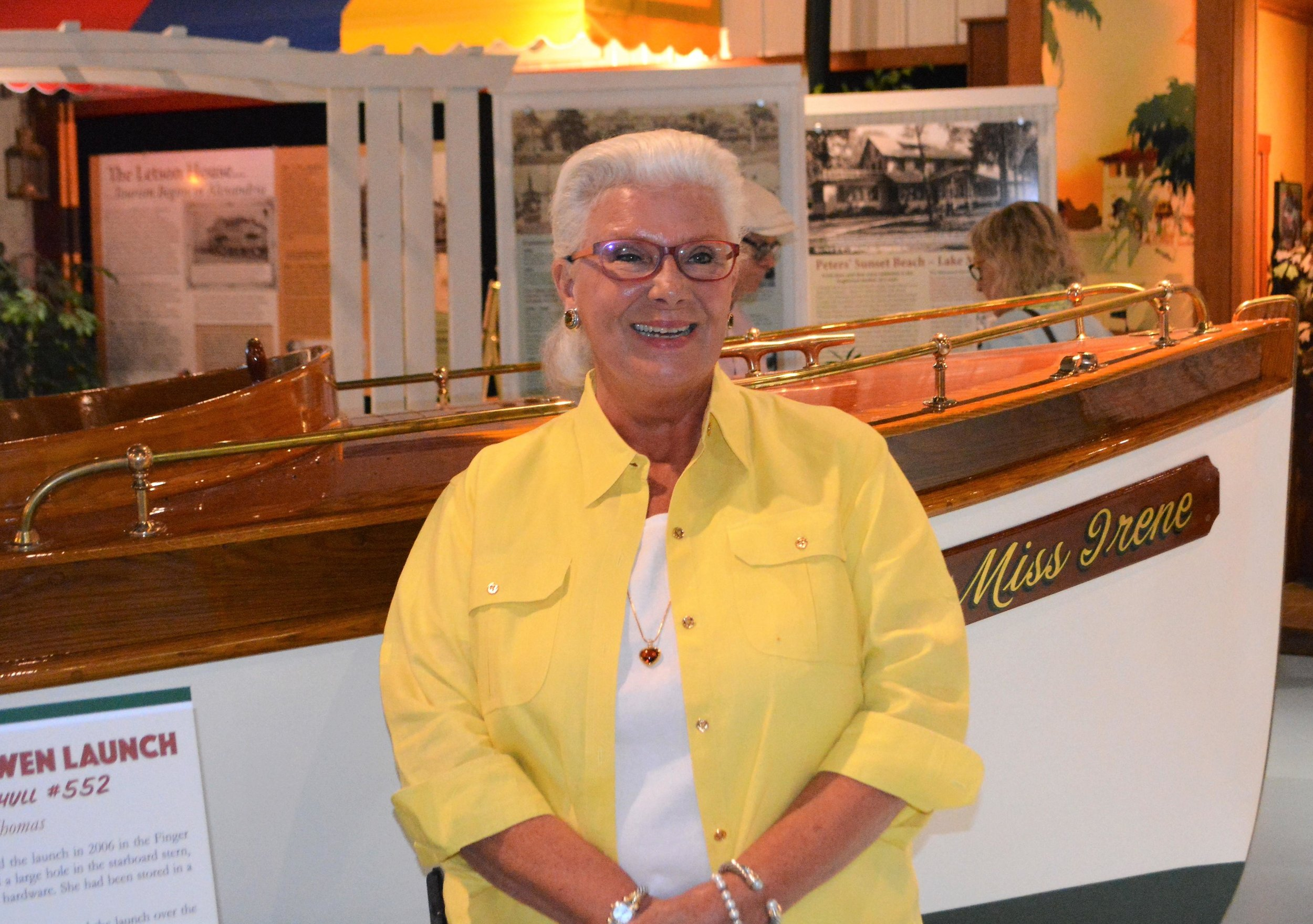 Betty Thomas poses next to one of two boats she donated to the museum with her husband, Jack, who died last year. Thomas was honored at a reception last week. (Ross Evavold / Echo Press)