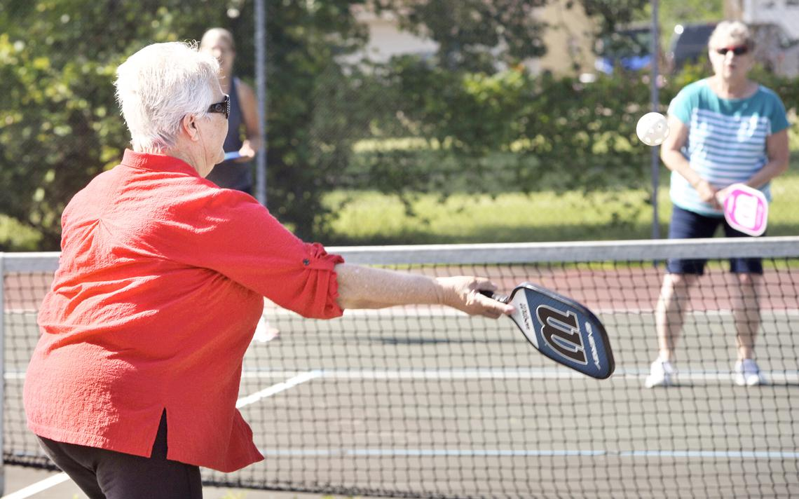 Pat Dahlhiemer (left) hits the ball across the net to Lynne Bowman Bolles during a pickleball clinic conducted by staff from the Alexandria Senior Center last week in the tennis court at Alexandria City Park. Organizers of the clinic hope to develop more interest in the game, which is a combination of tennis, ping-pong and badminton. (Lowell Anderson / Echo Press)