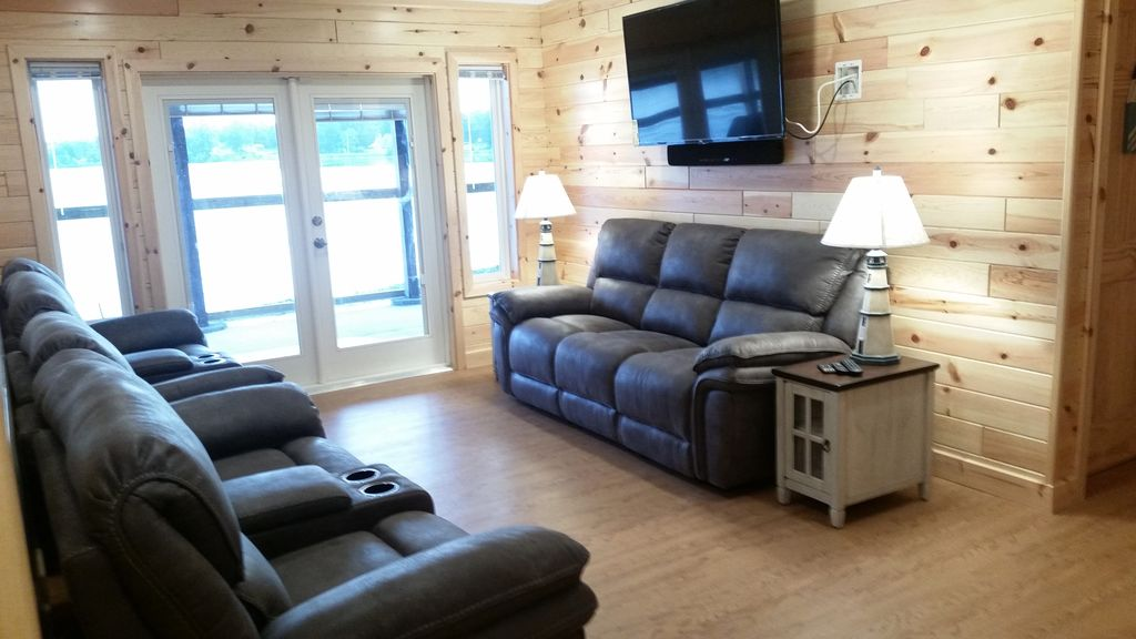 """Walk-out level TV Room seats 7 w/ pwr recliners, 55"""" 4K TV, views of Stone Lake."""