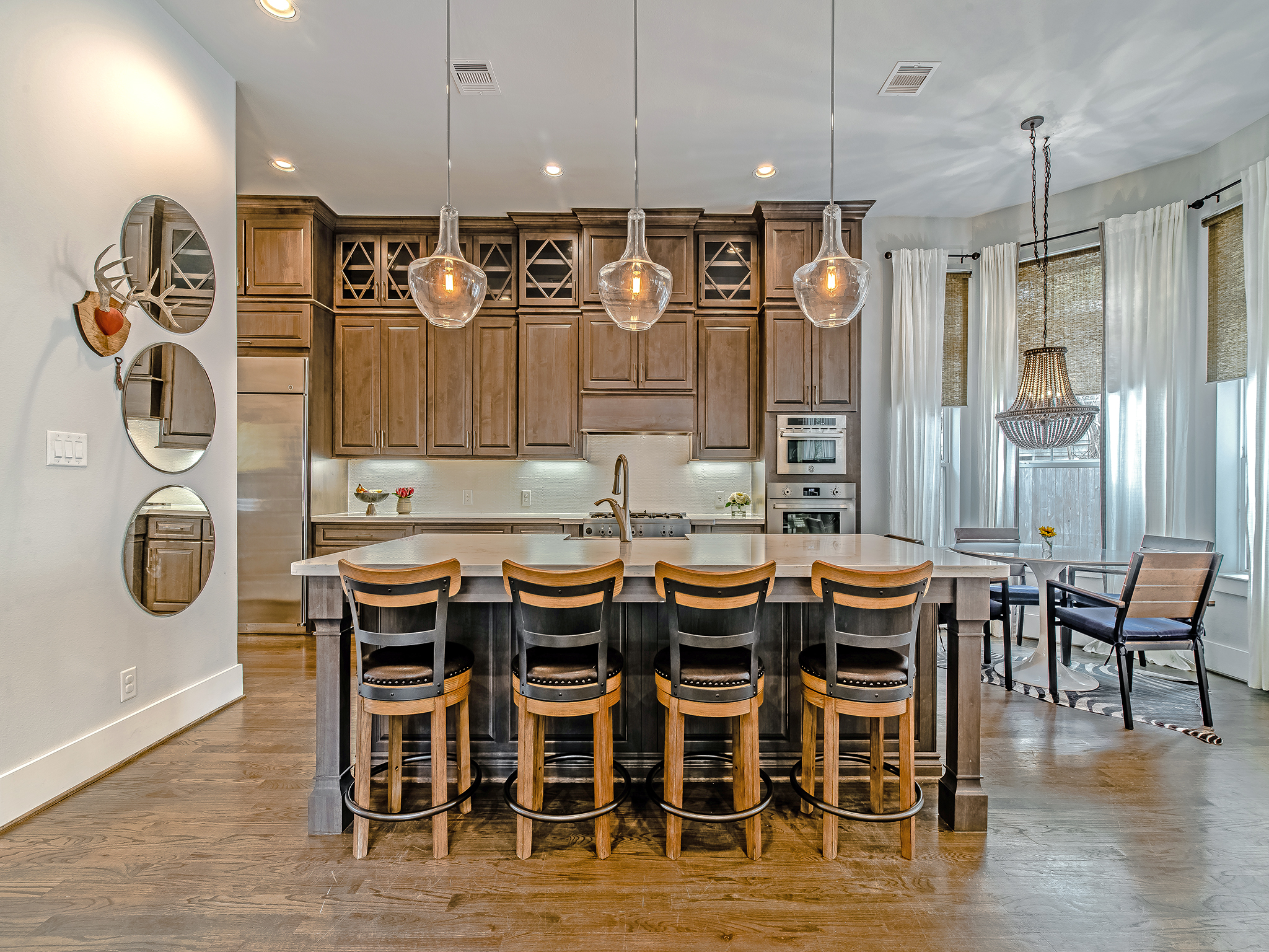 Ample island seating, breakfast nook, designer lighting make this kitchen a dream for entertaining.