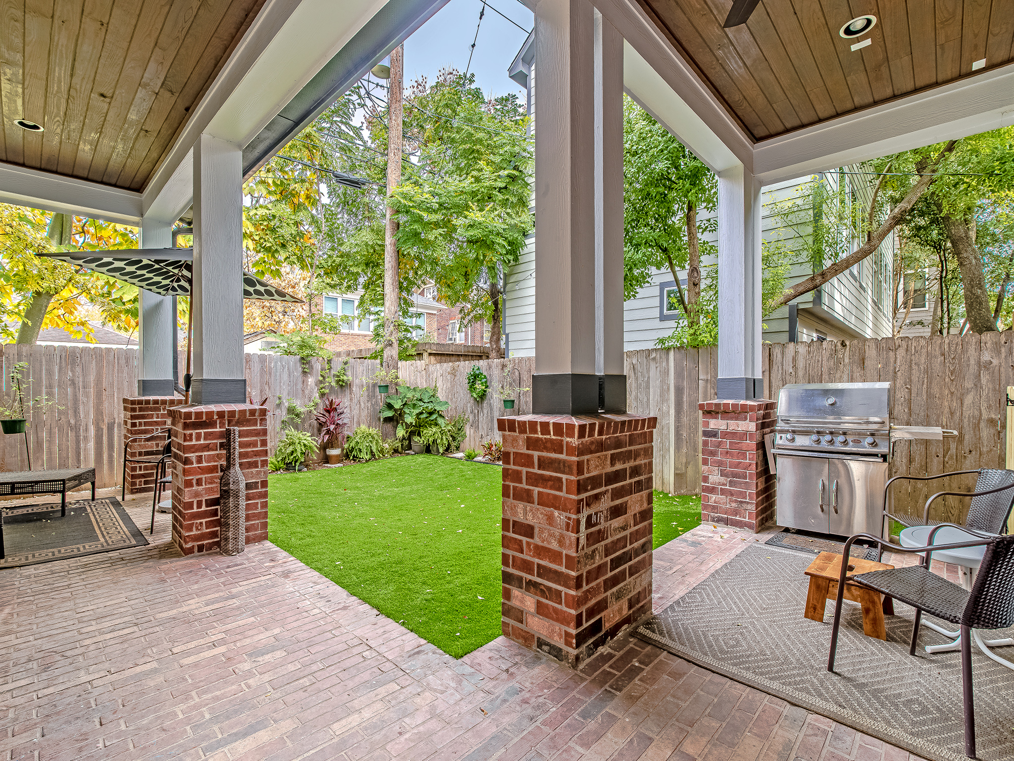 Gorgeous backyard features ample patio space, turfed play space and flower beds.