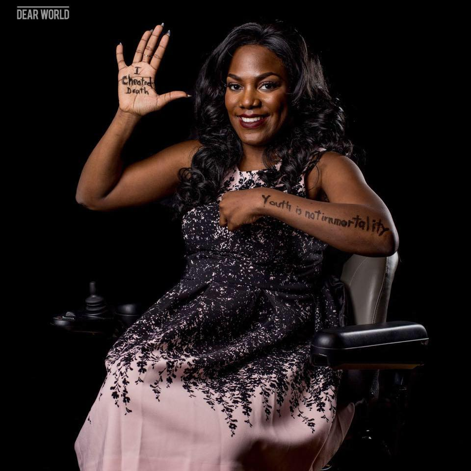 "ola ojewumi motivating the disabled, on her palm is written ""i cheated death"" and ""youth is not immortality "" is written on her wrist"