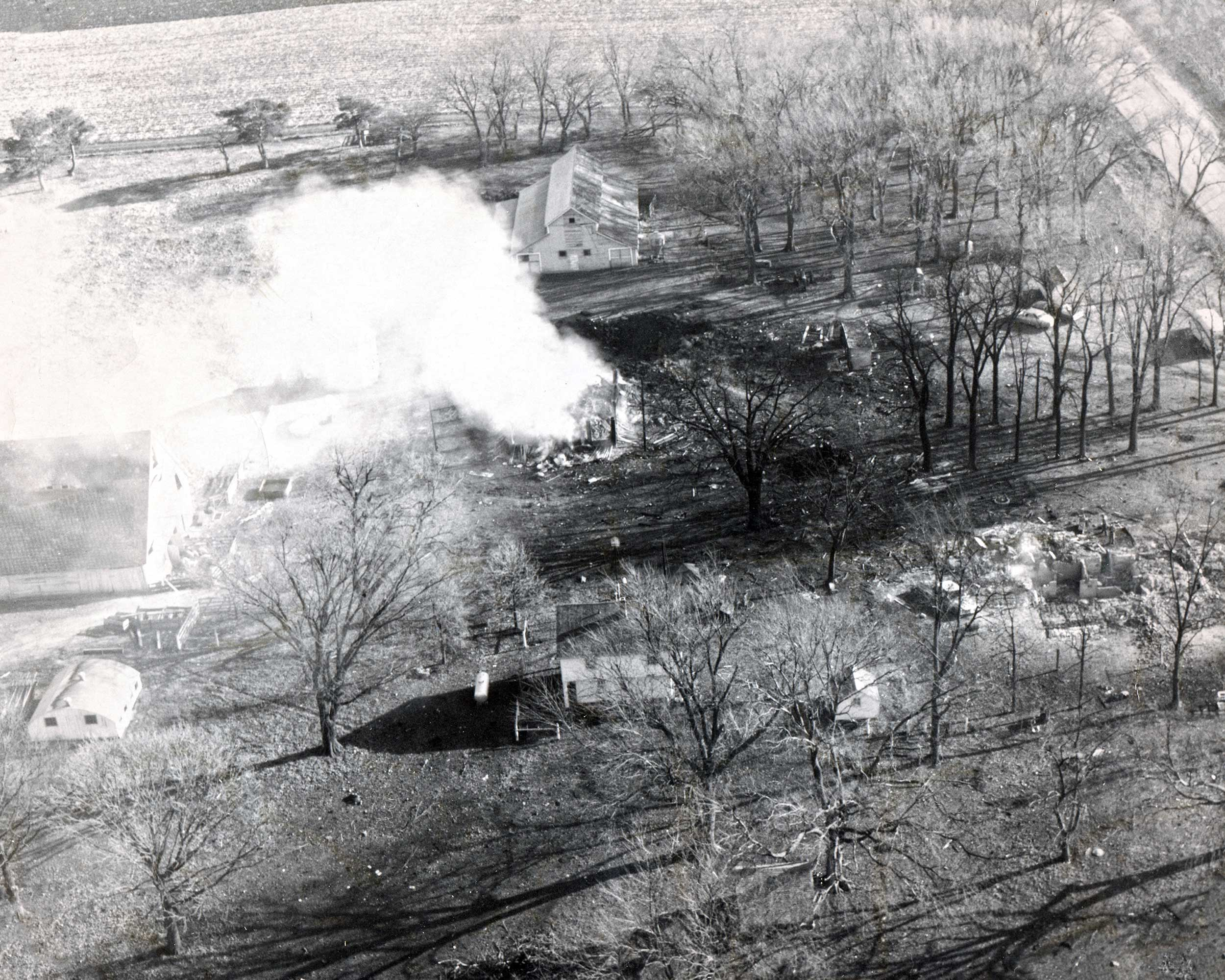 Follinglo Farm Destruction - Aerial photo taken from over I-35 looking East over the farm. The corncrib burns in the center of the photo with the crater from the explosion just visible through the smoke to the East beyond. The remains of the devastating house fire are visible in the lower right third of the photo.
