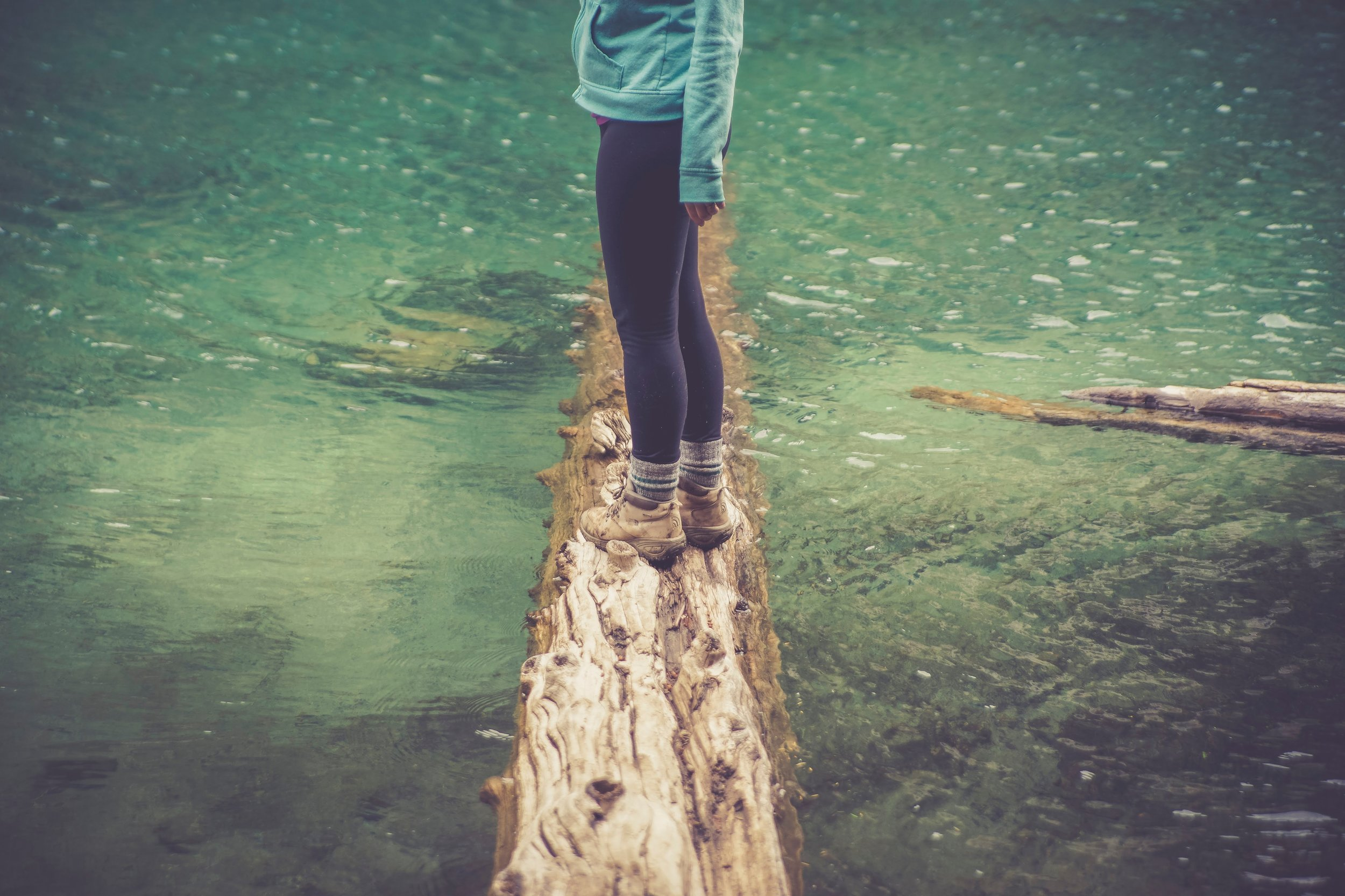 woman standing on a log in a river
