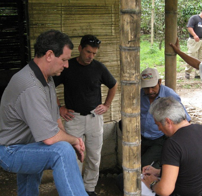 JIm Dulin works with FLF team members on the porch of a bamboo home built by FLF.
