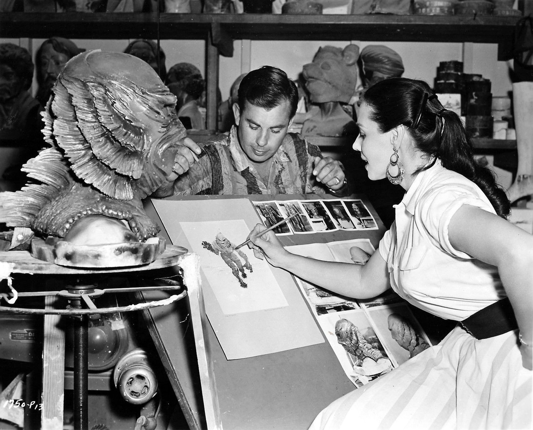 "Milicent Patrick creating watercolor artwork of the Gill Man, with jealous asshole Bud Westmore ""supervising."" 
