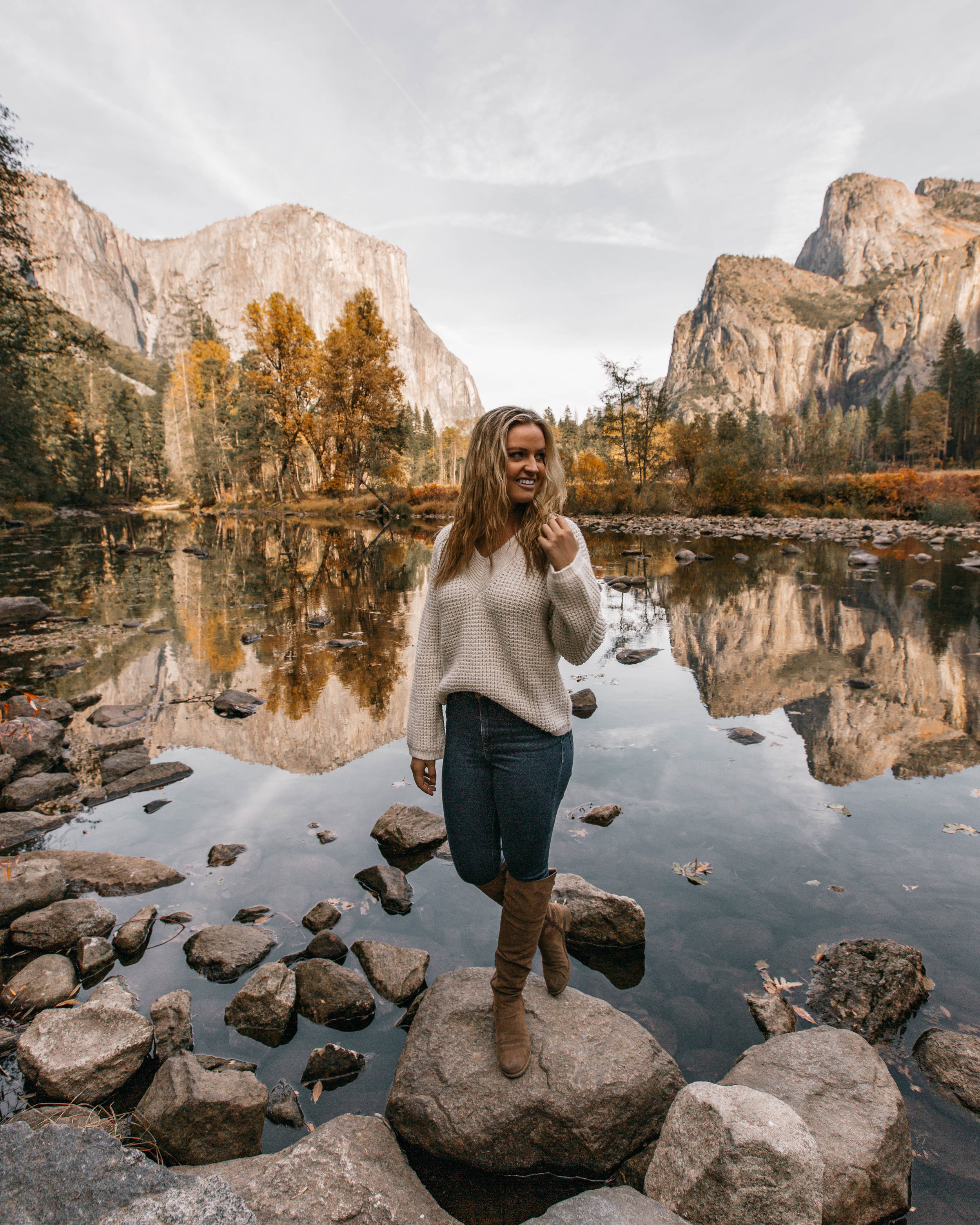 In frame: Nicole Renard @nicole_thenomad in front of a view of Yosemite Valley. El Capitan is behind her to the left!