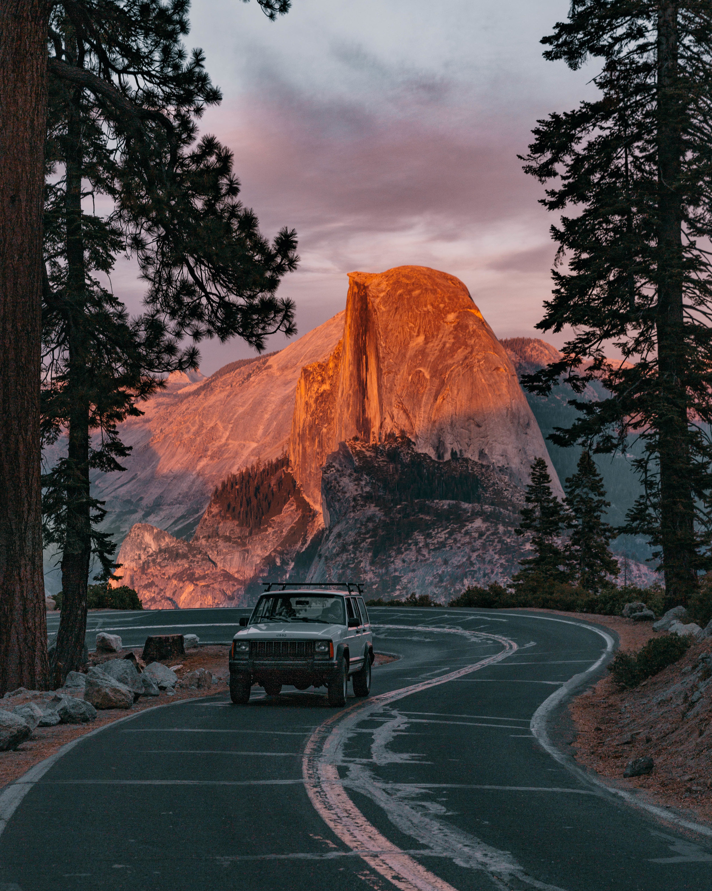 A an old '98 Jeep in front of the iconic Half Dome. If you stay past sunset, watch the dome for twinkling lights of climbers trying to reach the summit.