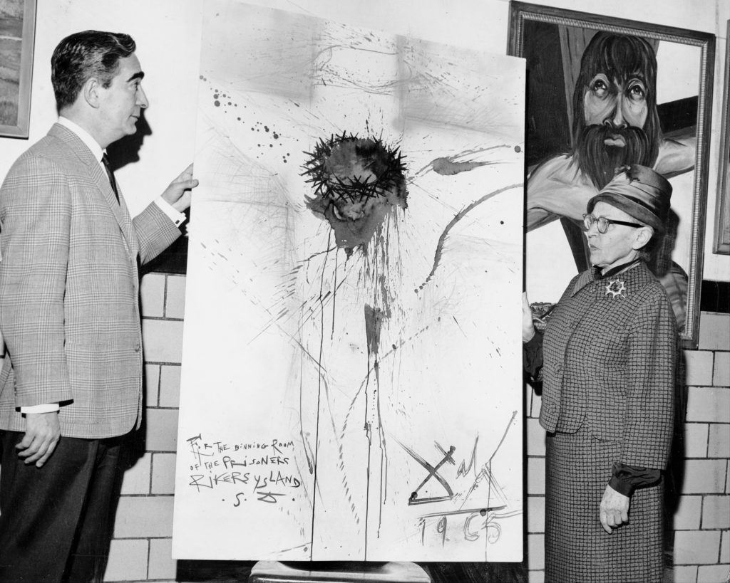 """Nico Yperifanos, Salvador Dali's personal representative, presents artist's 'Christ on the Cross"""" to Rikers Island prison. Correction Commissioner Anna Kross accepts the work. The Dalí painting was stolen by prison guards in 2003. Photo by Leonard Detrick/NY Daily News Archive via Getty Images."""