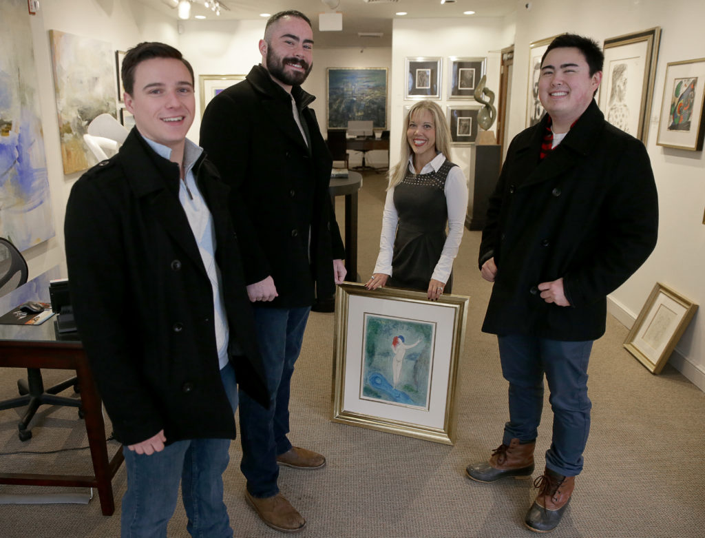 Galerie d'Orsay co-owner Sallie Hirshberg holds a painting involved in an attempted theft which was foiled by Boston University Students Chris Savino, far left, Mackenzie Thompson, second from left, and Jesse Doe, far right. Courtesy of Jonathan Wiggs/The Boston Globe via Getty Images.