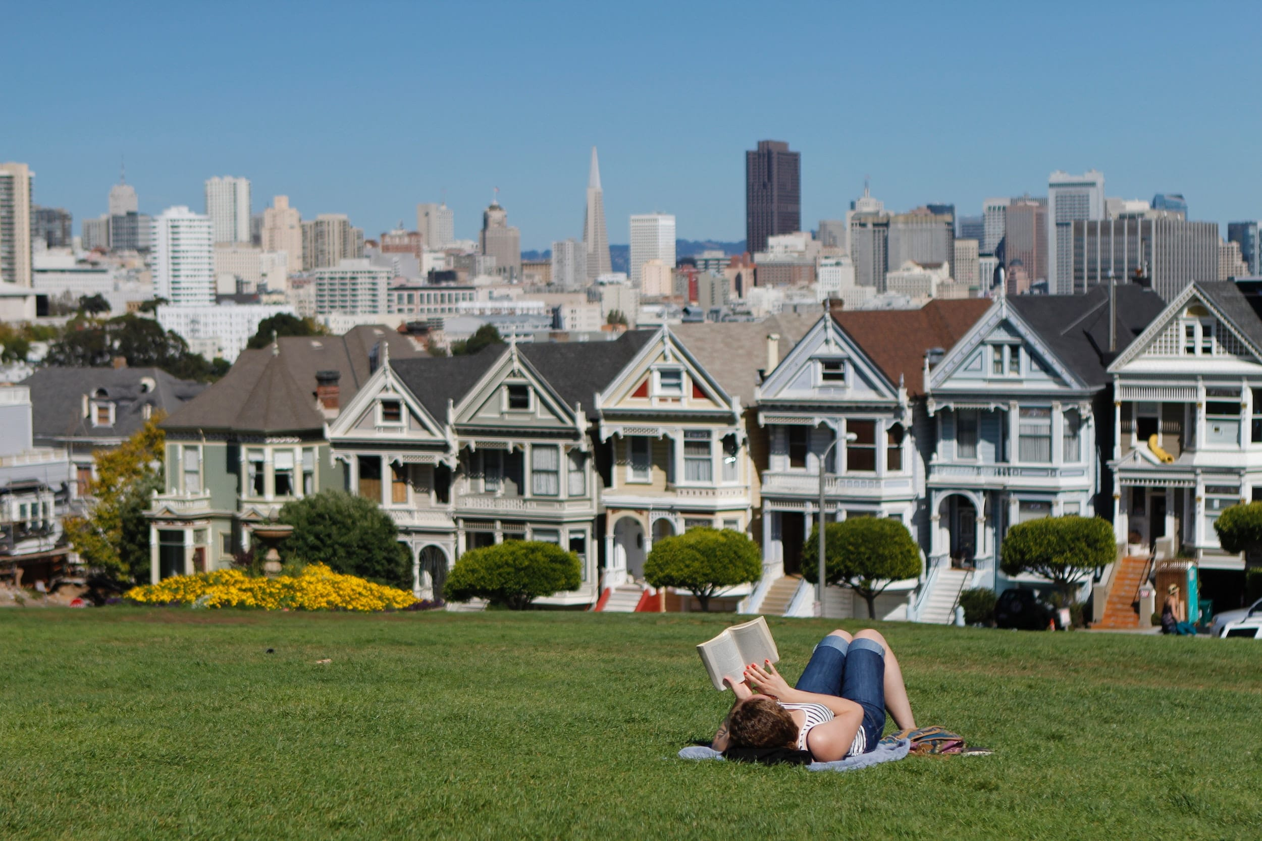 A woman lying down on grass and reading a book in front of San Francisco houses.