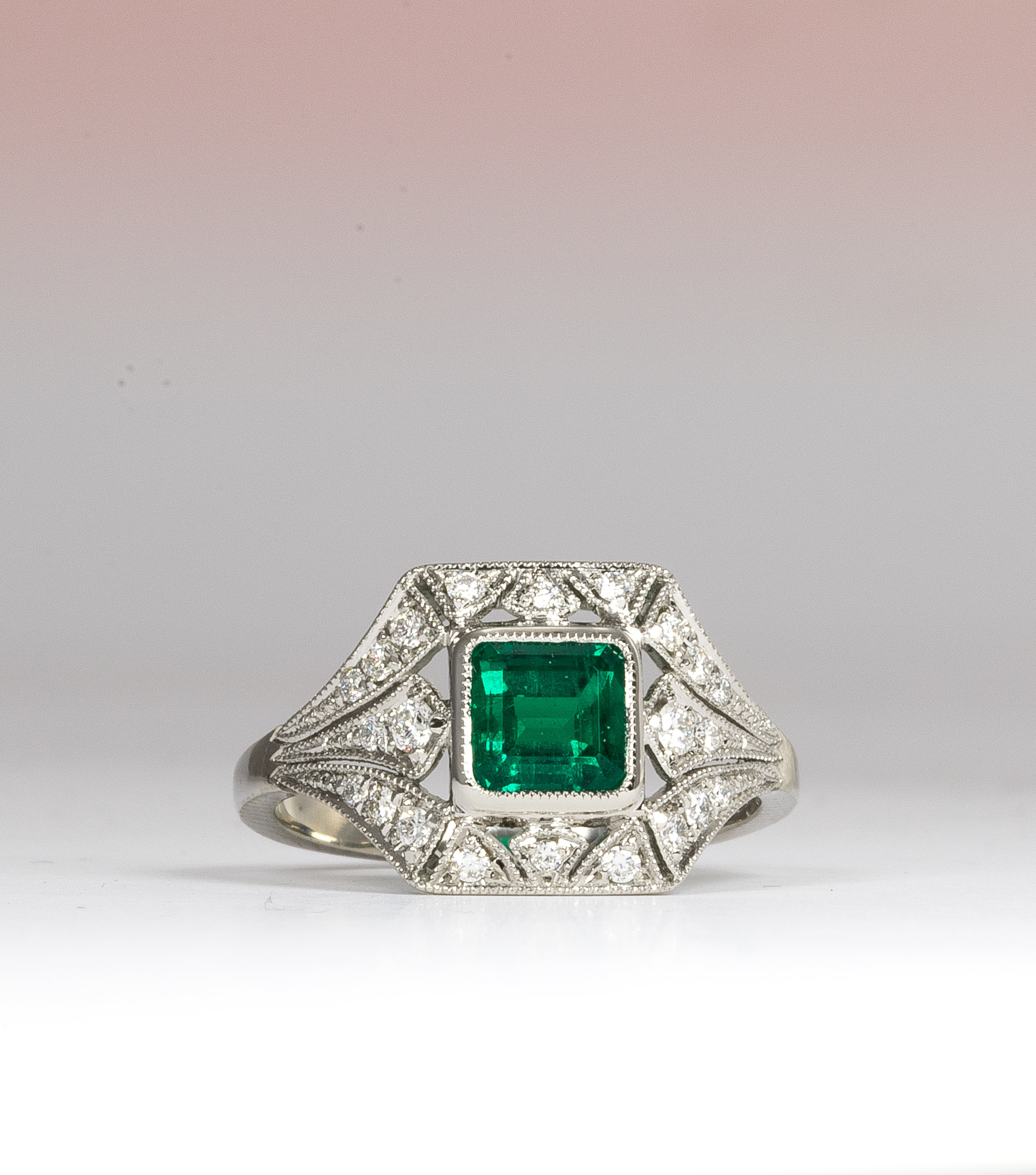 Fine quality emerald set 1920's style cluster ring. - Our client had found the image of an antique emerald ring online that she liked the look of but wanted a deeper green, more lustrous emerald. After searching and finding the perfect stone, we designed the new platinum ring with a heavier shank and a slightly more robust head. We did this to cope with the more active, busy life of our customer but still managed to maintain the delicacy of design that jewellery from this period had.