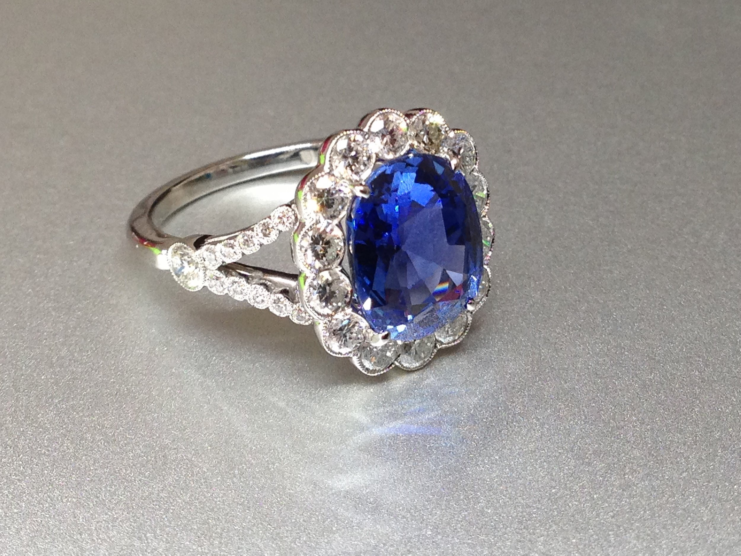 Copy of Platinum mounted sapphire and diamond 1920s style cluster with split shoulders. Made in Chichester, England.