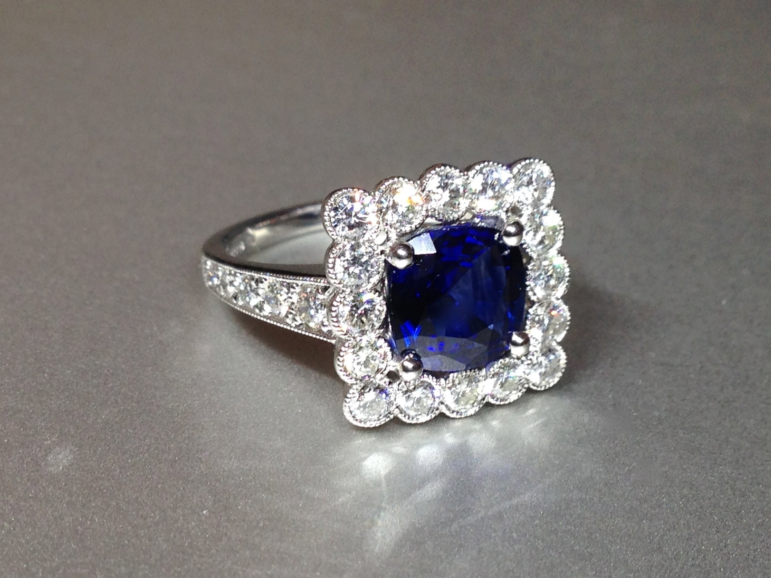 Copy of 2.08ct cushion cut sapphire in 1920's style daisy edge millegrain  cluster ring. Made in Chichester, England.