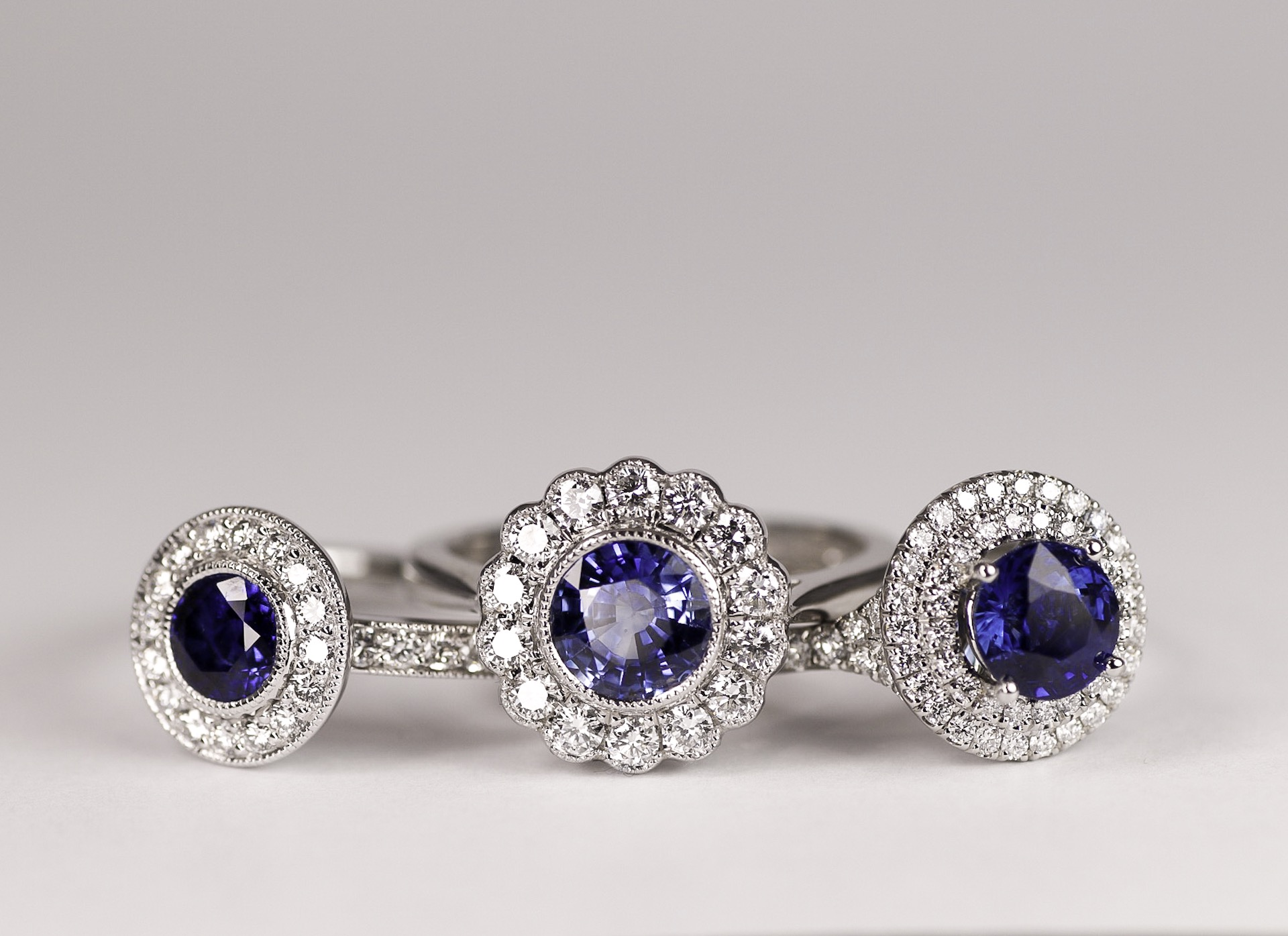 18ct white gold and platinum mounted diamond and sapphire cluster rings. All three made in Chichester, England.