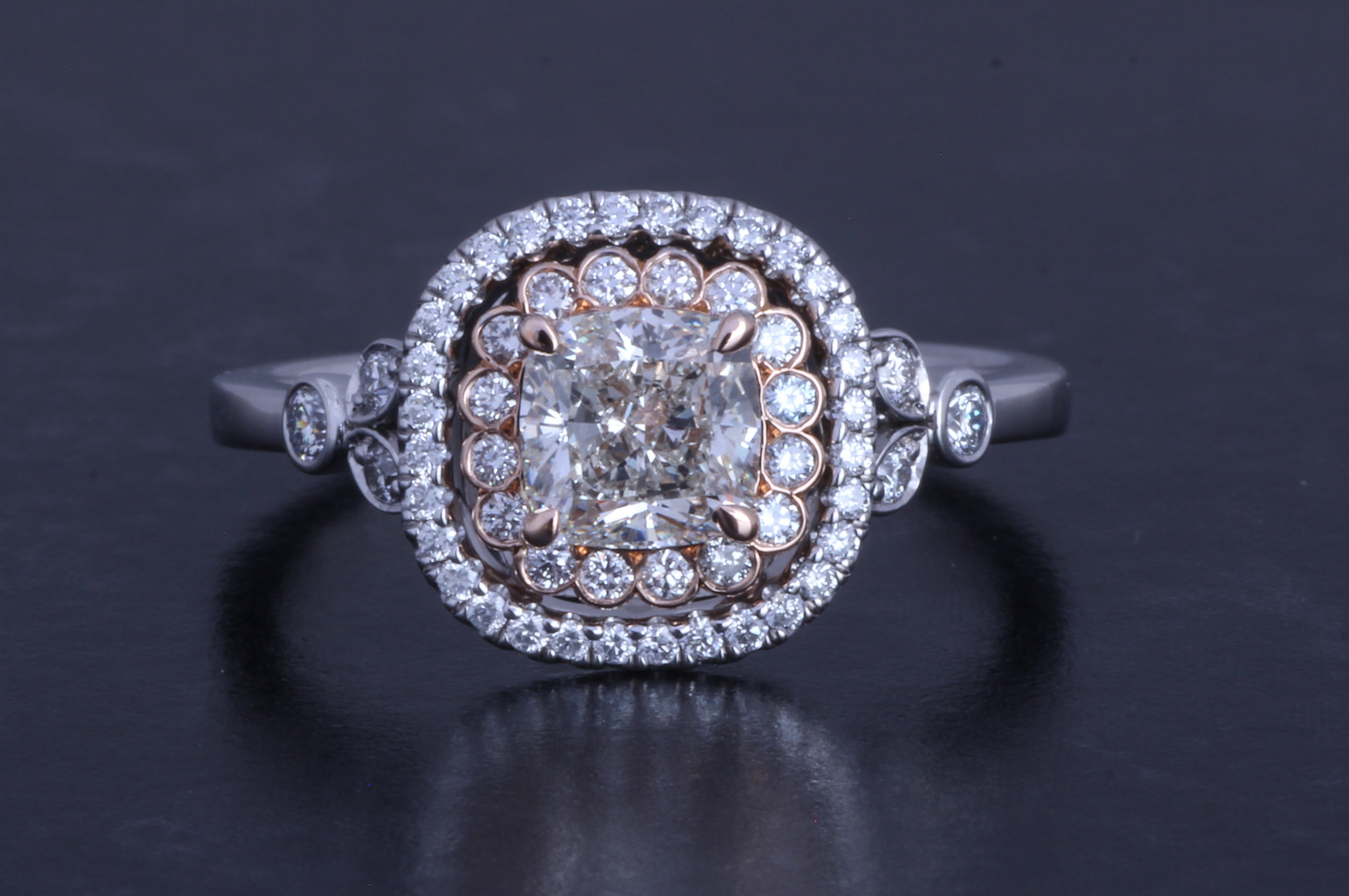 Platinum and rose gold mounted cushion cut and brilliant cut diamond cluster ring. Made in Chichester, England.