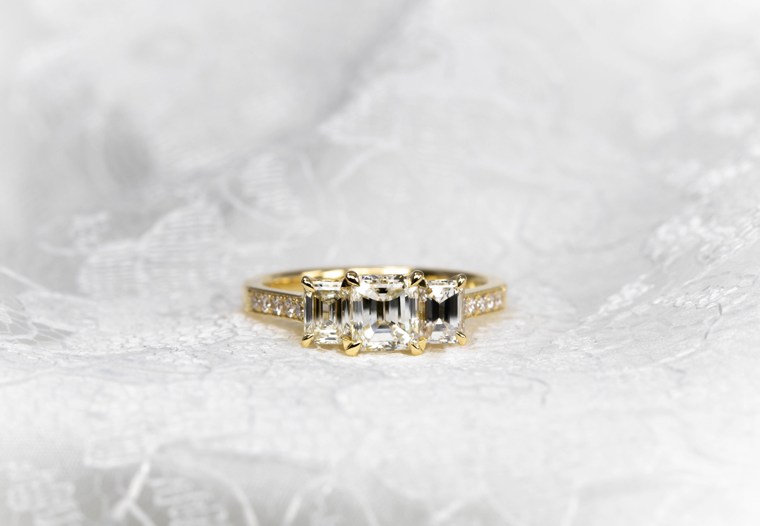 Copy of 18ct yellow gold mounted three stone emerald cut diamond ring with grain set shoulders. Made in Chichester, England.