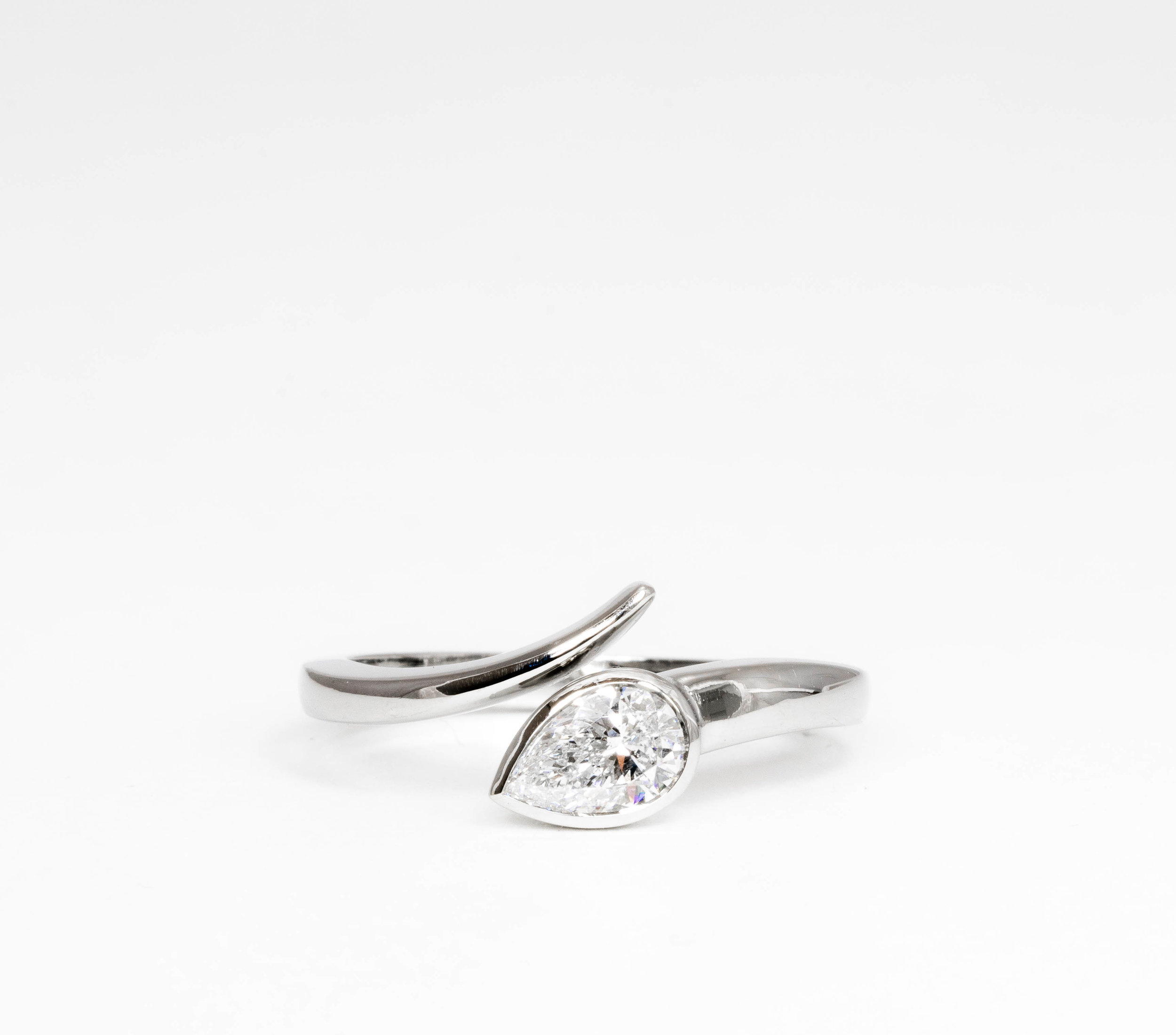 Copy of Platinum mounted pear shaped diamond, rub-over set twist ring. Made in Chichester, England.