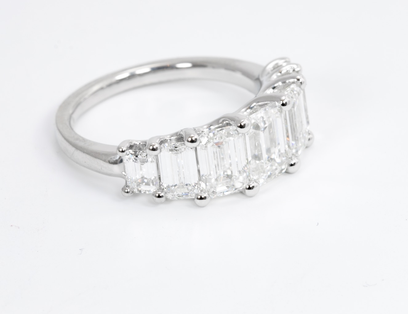 Copy of Graduating seven stone emerald cut diamond half hoop ring in U-shaped collet mount. Made in Chichester, England.