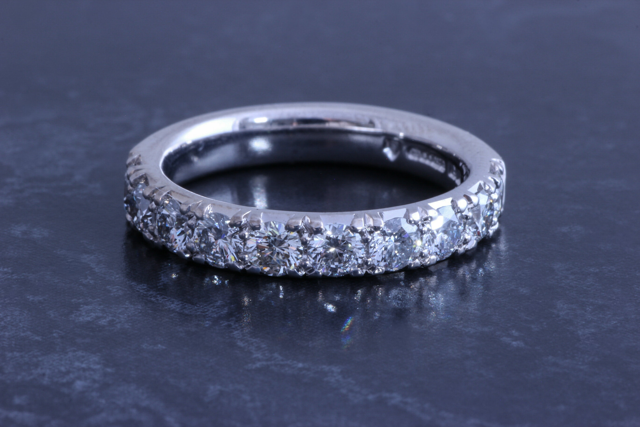 Copy of Platinum mounted half eternity ring with cut away setting.
