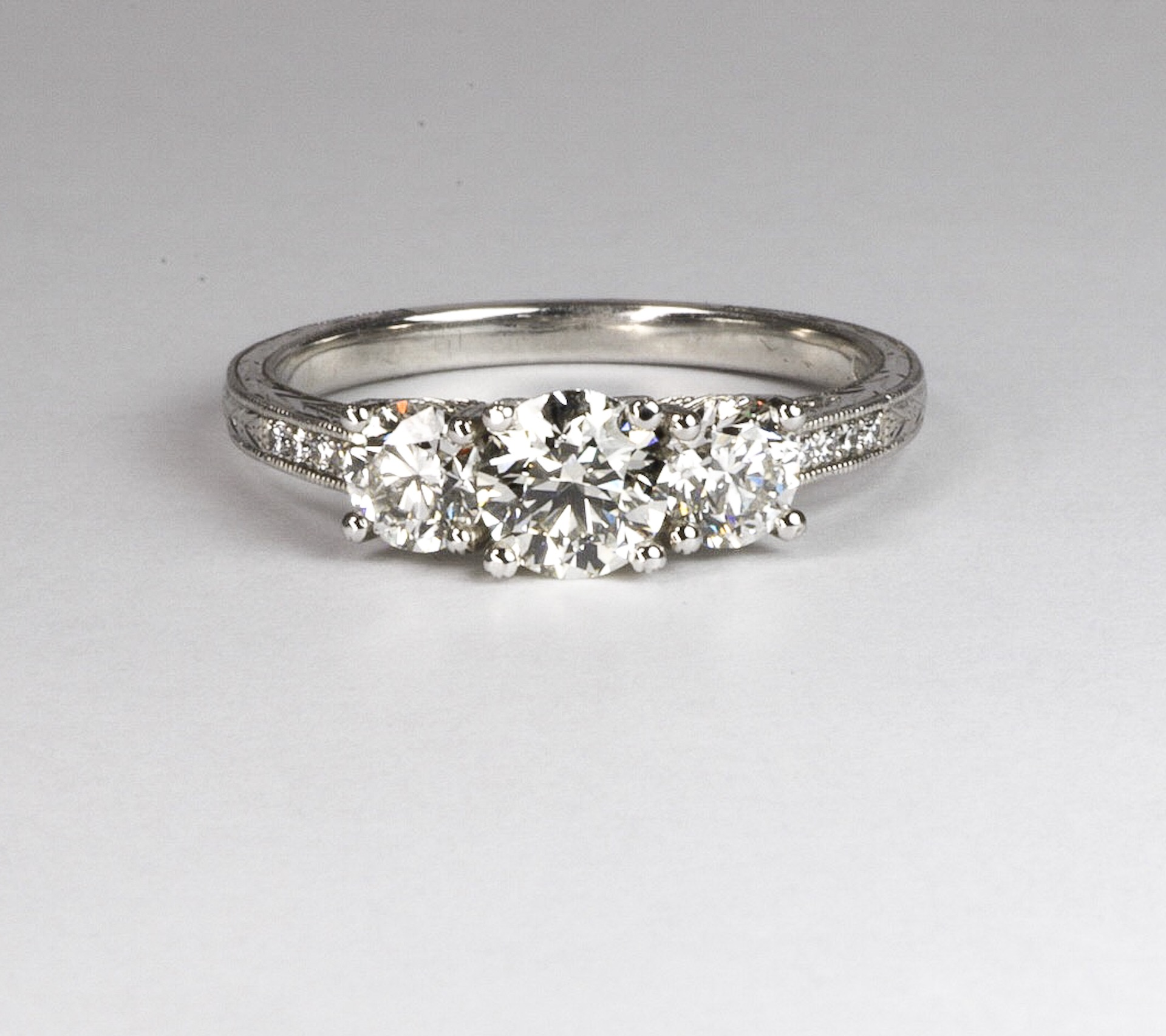 Copy of Platinum mounted modern style diamond three stone ring with grain set diamond set shoulders.   Made in Chichester, England.