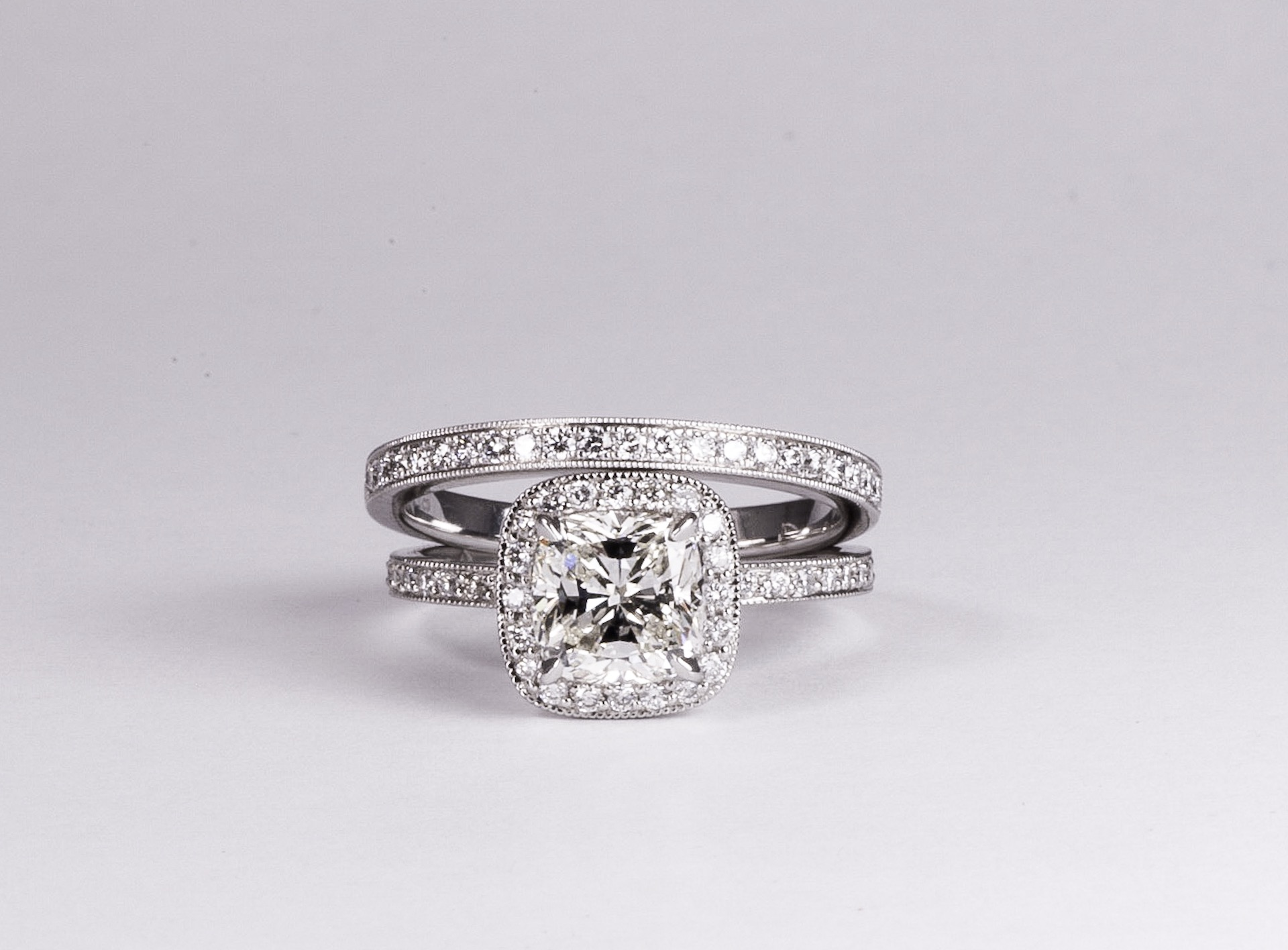 Copy of Cushion cut diamond with grain set diamond surround and shoulders finished with millegrain edge decoration. Made in Chichester, England.