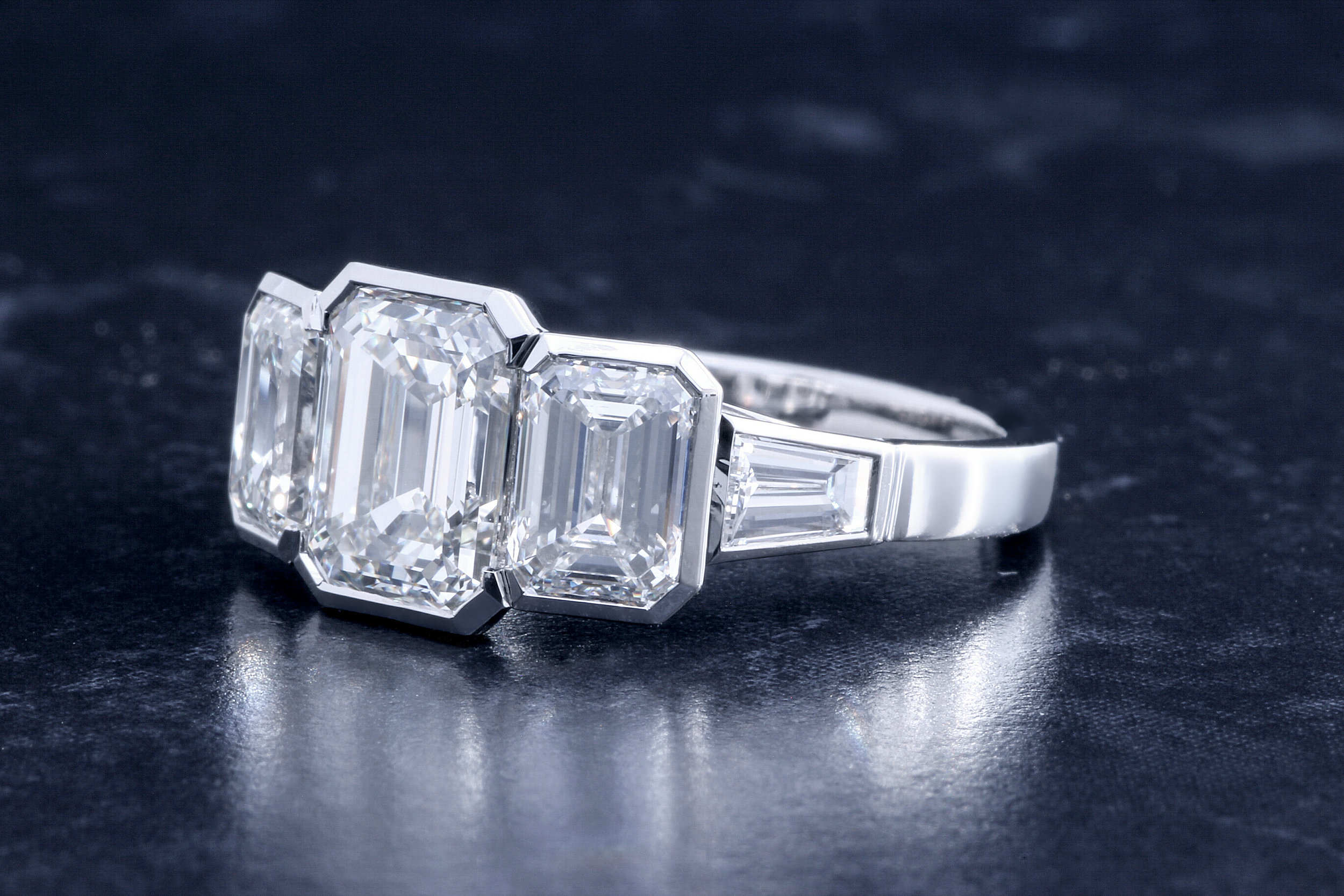 Copy of Fabulous three stone emerald cut diamond ring with tapered baguette shoulders. Rub-over set in precision made platinum mount. Made in Chichester, England.