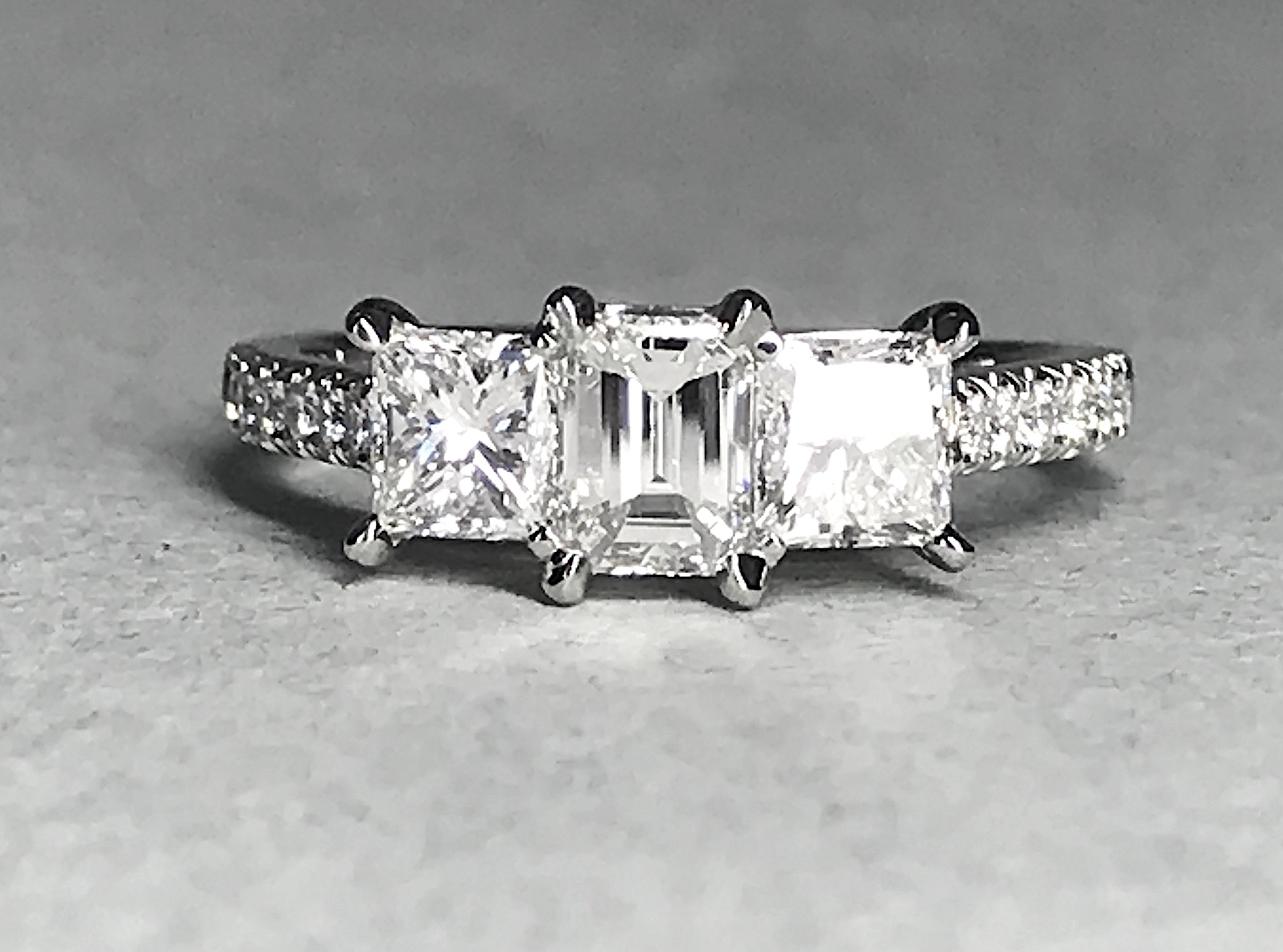 Copy of Emerald and princess cut diamond 3 stone ring with cut away set diamond shoulders. Made in Chichester, England.