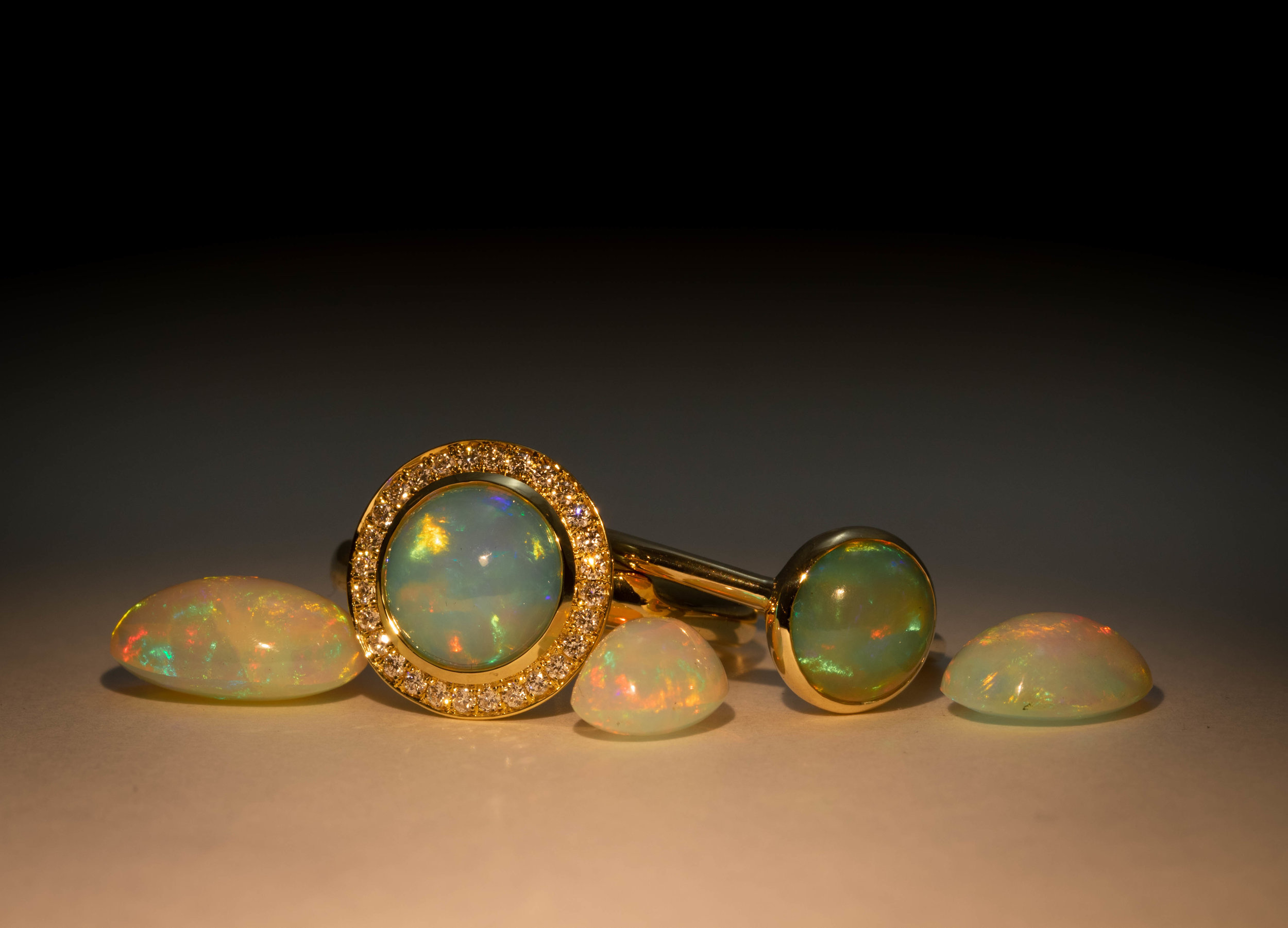 A selection of Opals from our stone stock alongside an Opal Halo cluster and rub over set Opal solitaire set in Yellow Gold. Made in Chichester, England.