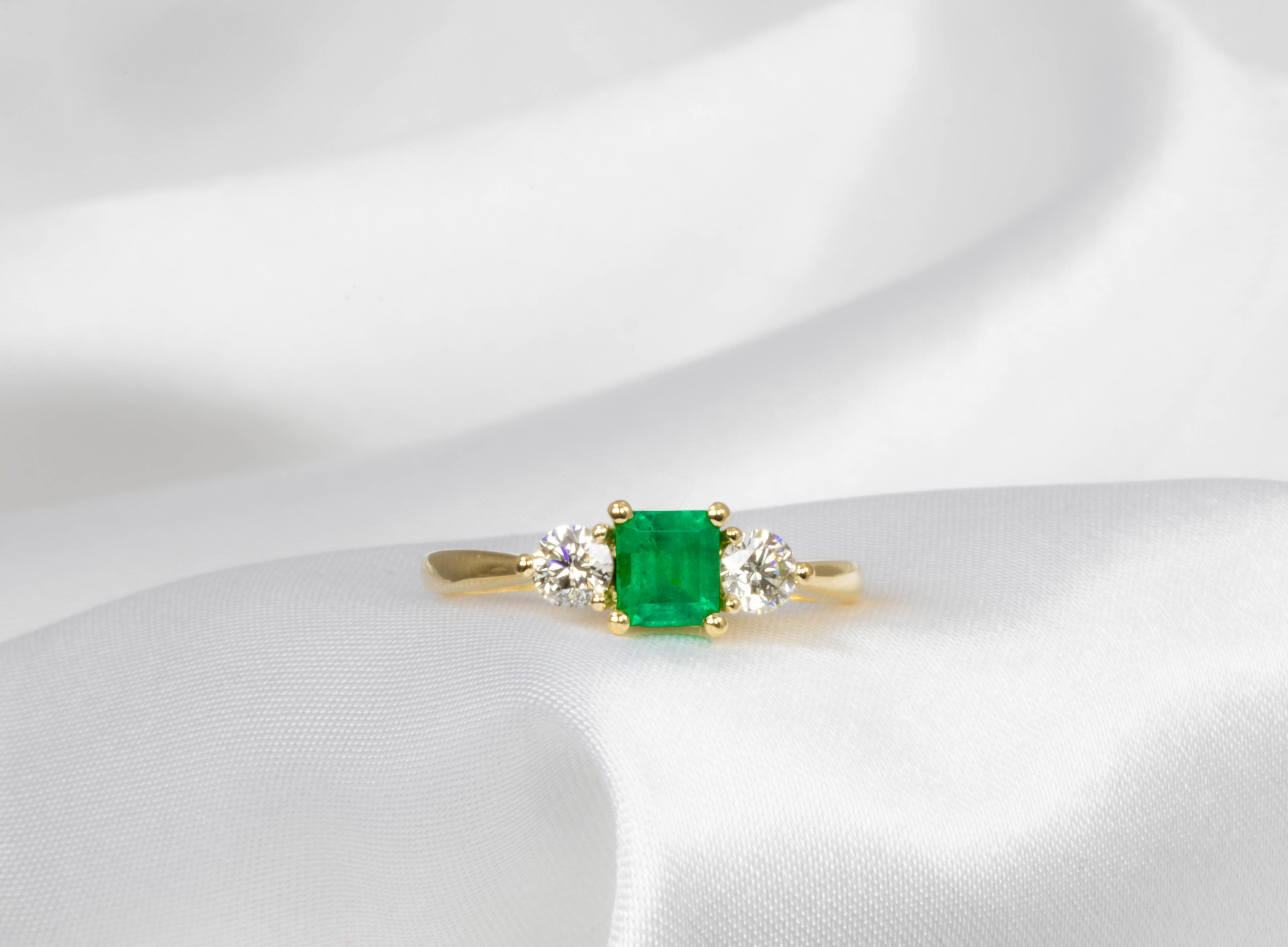 Princess cut Emerald and Diamond 3 stone engagement ring. Made in Chichester, England.
