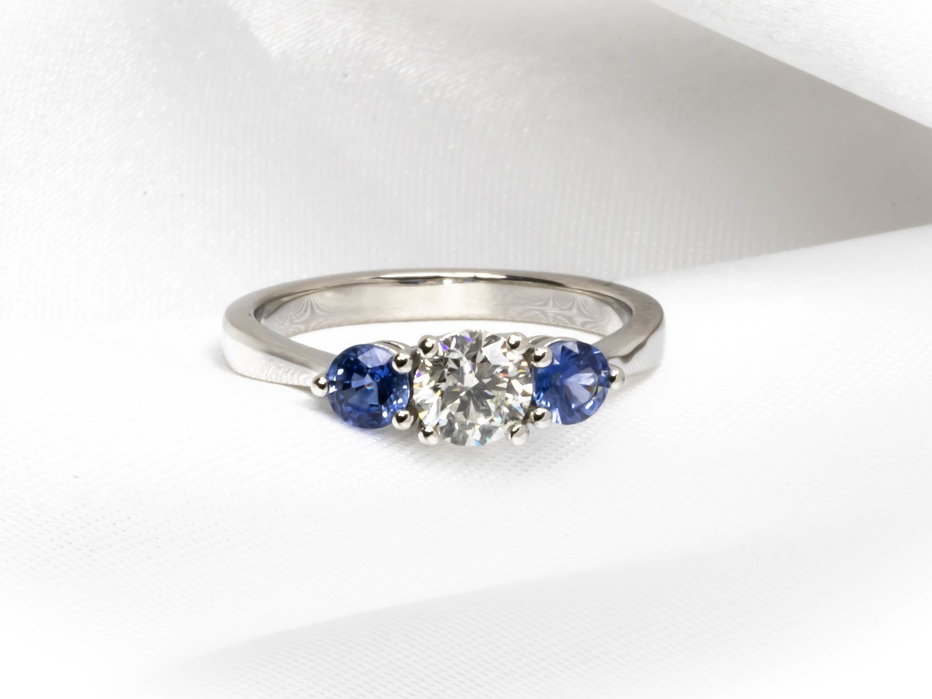 Modern style claw set platinum mounted diamond and sapphire three stone ring. Made in Chichester, England.