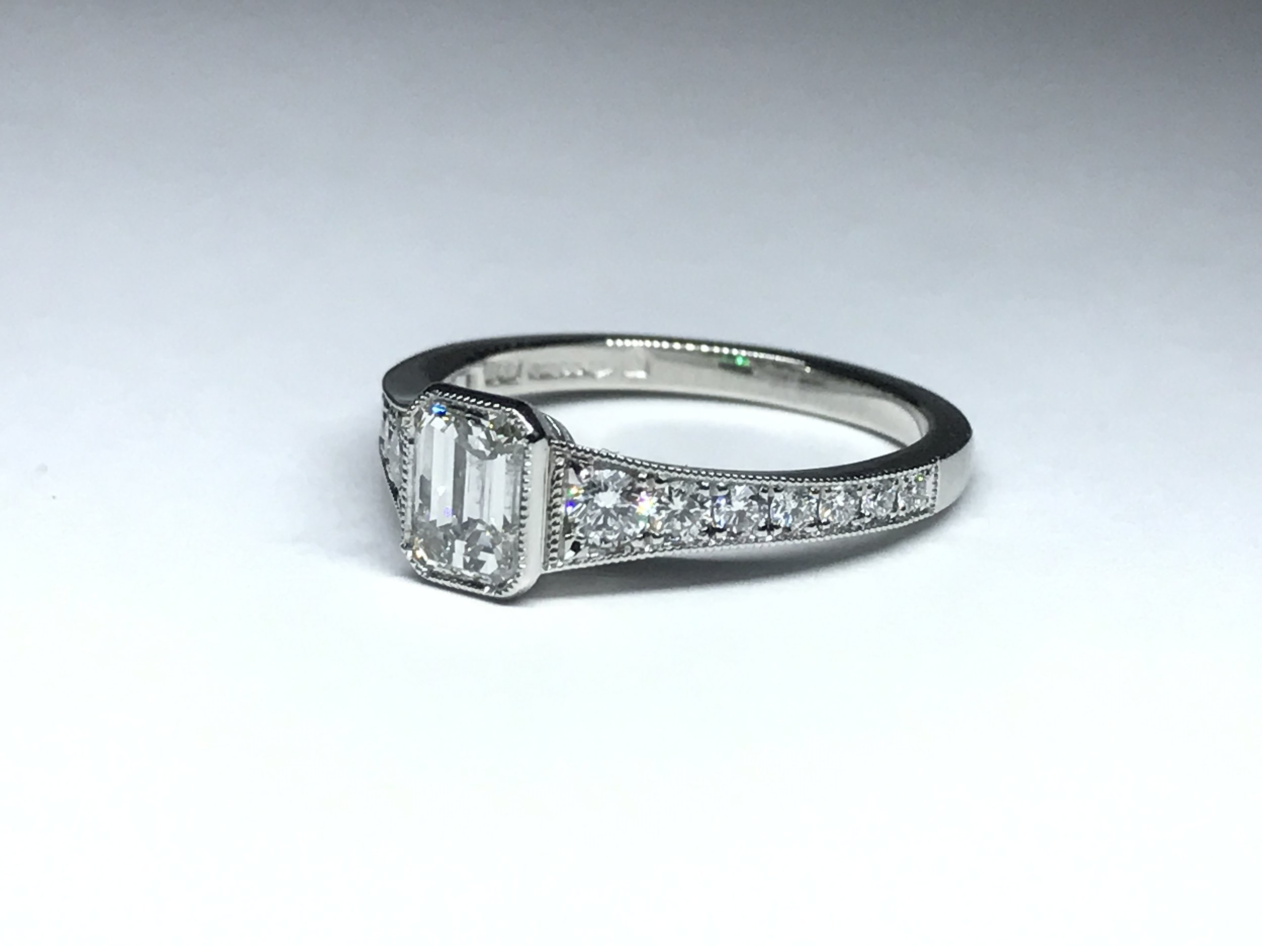 Copy of Rub-over set emerald cut diamond with graduated grain set diamond shoulders. Made in Chichester, England.