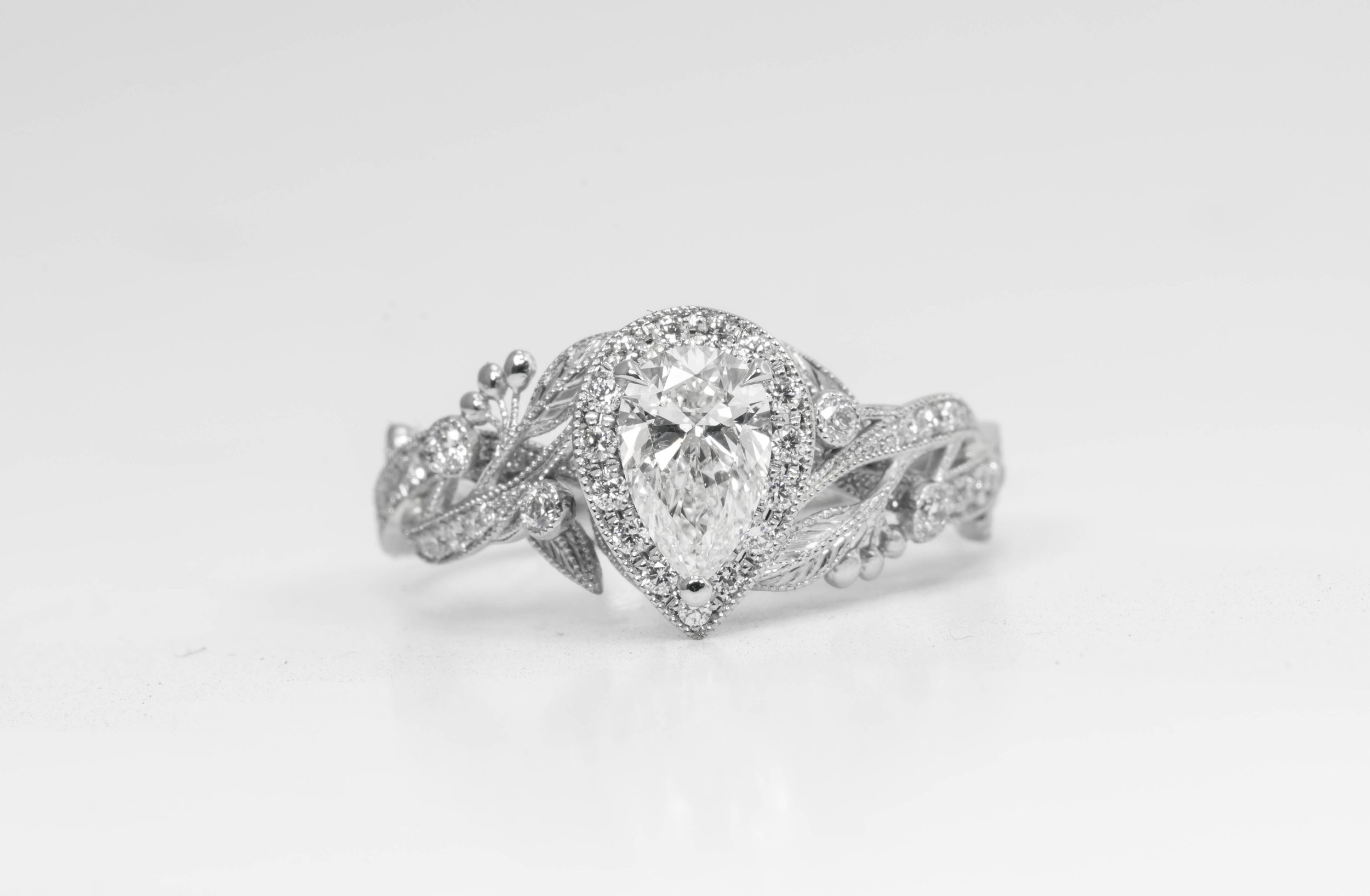 Platinum mounted pear shaped diamond with foliate shoulders. Made in Chichester, England.