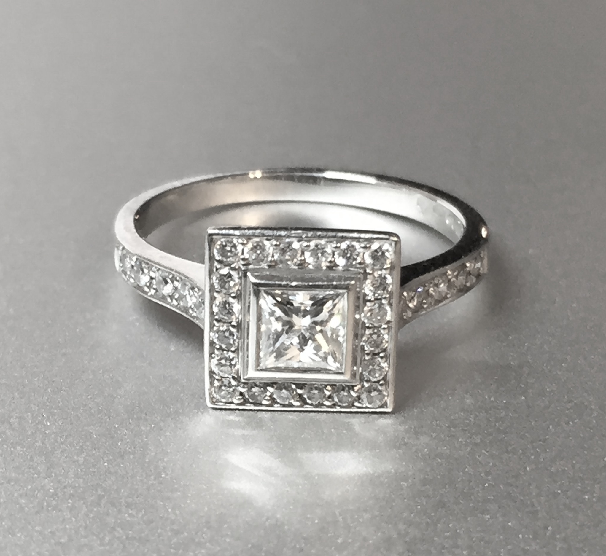 Copy of Platinum mounted princess cut centre and grain set diamond surround. Made in Chichester, England.