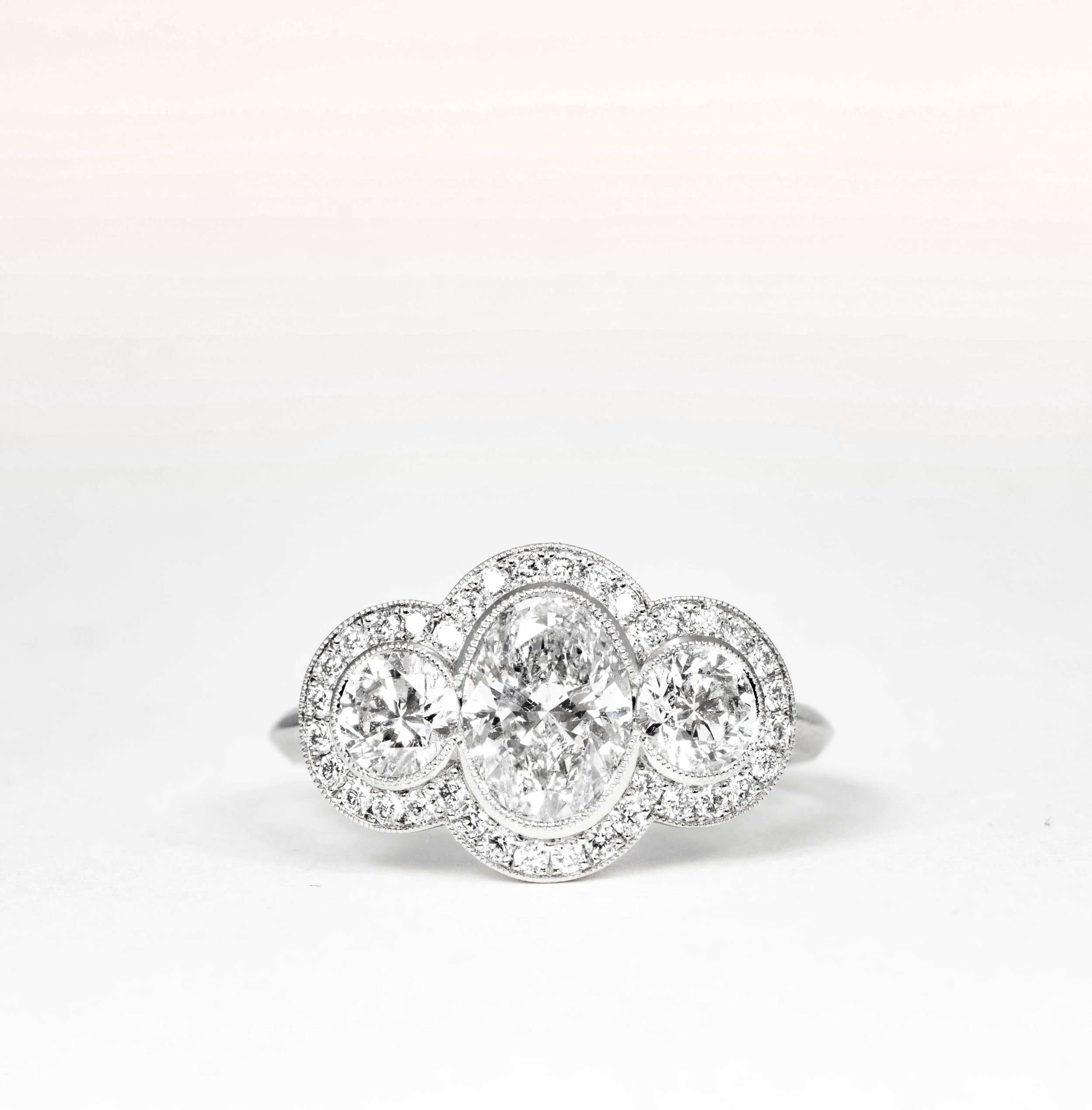 Copy of 1920's style oval diamond set triple cluster platinum ring. Made in Chichester, England.