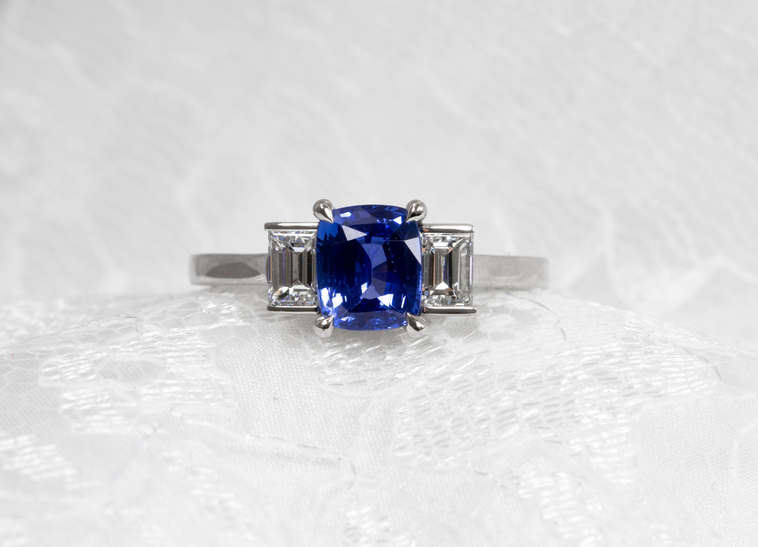 Platinum mounted cushion cut sapphire and wide baguette diamonds. Made in Chichester, England.