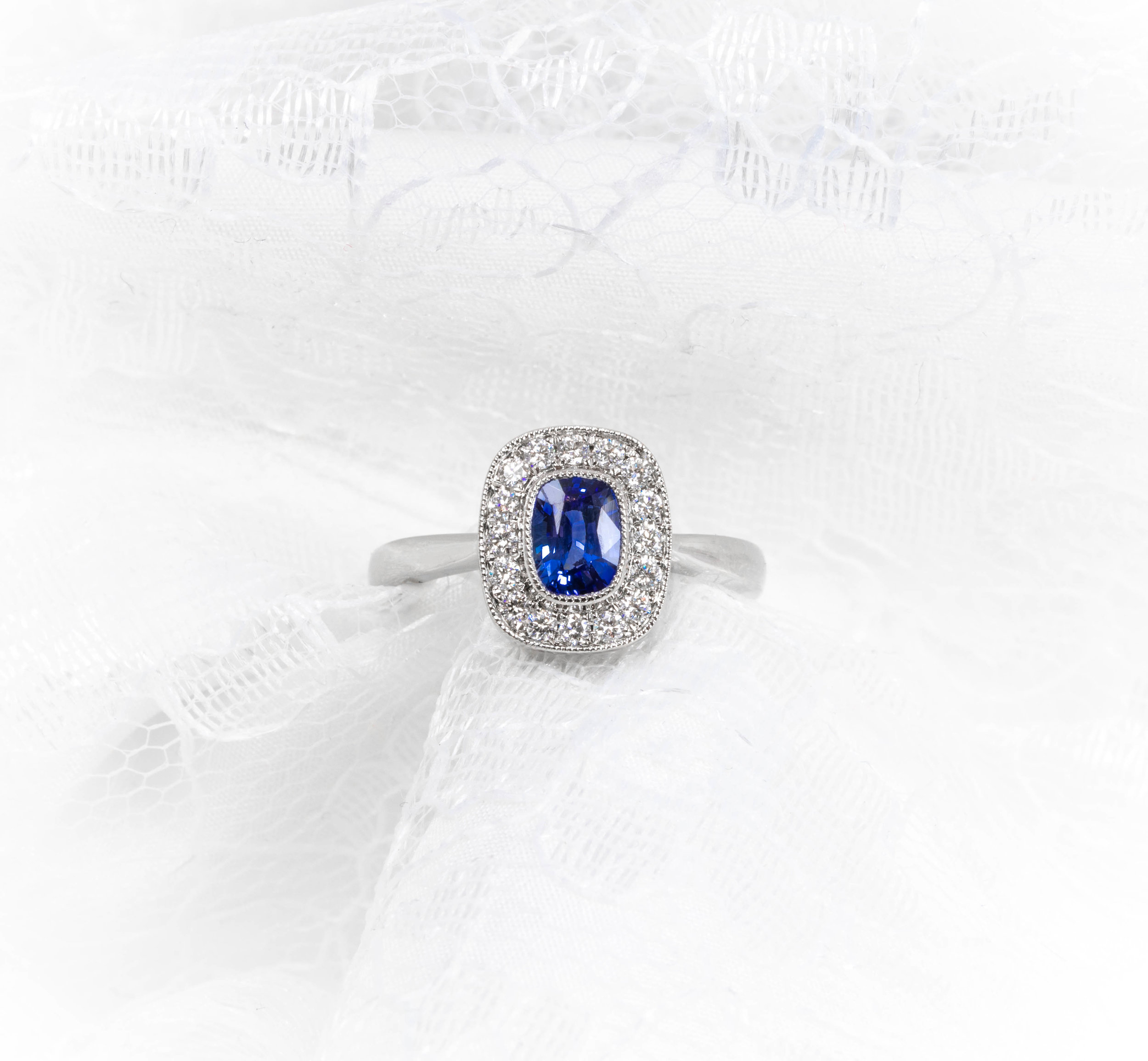 Oblong cushion cut sapphire and diamond platinum cluster ring. Made in Chichester, England.